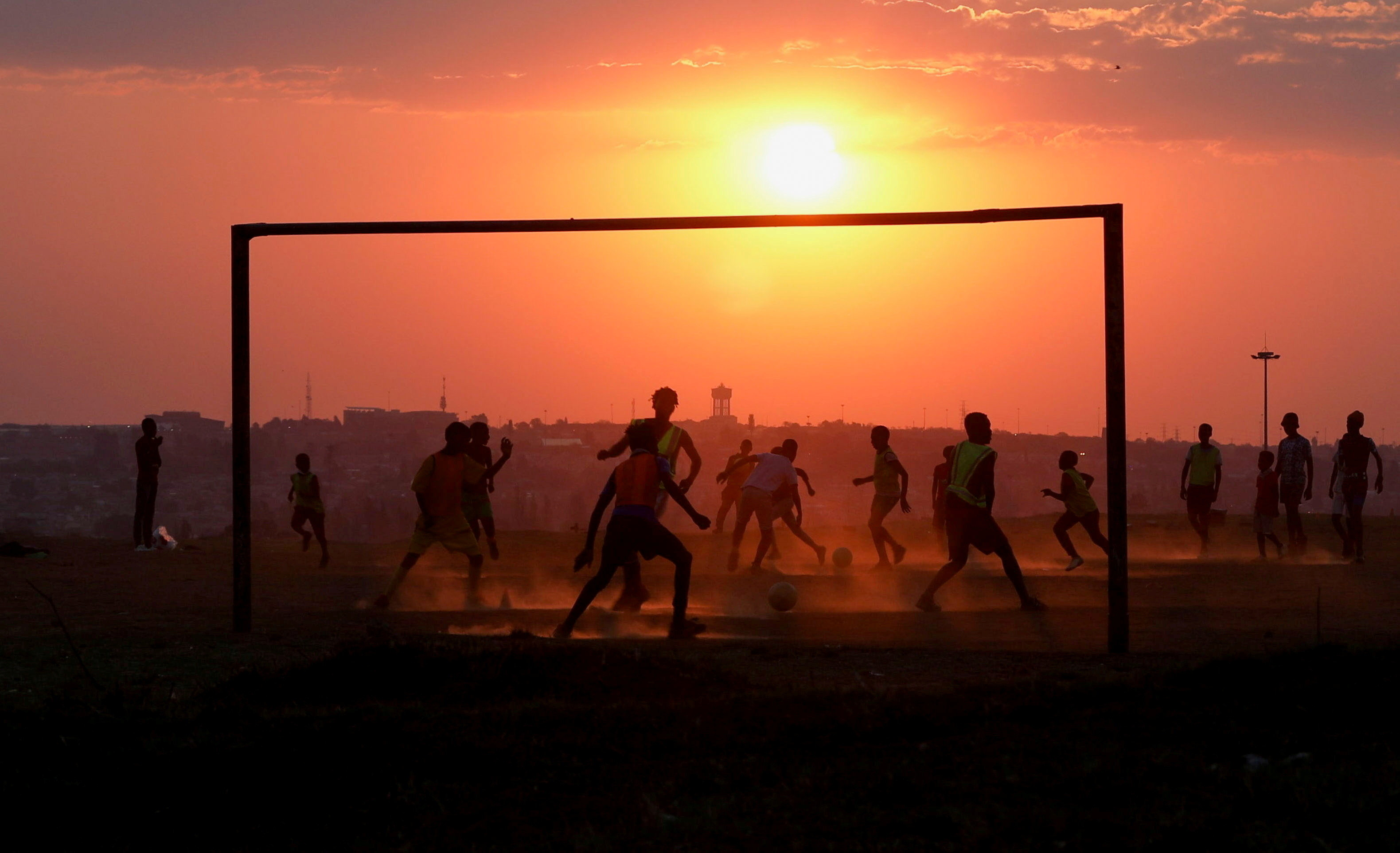 Locals play soccer on a dusty pitch in Soweto, South Africa, September 15, 2021. REUTERS/Siphiwe Sibeko     TPX IMAGES OF THE DAY - RC2GQP98G1B7