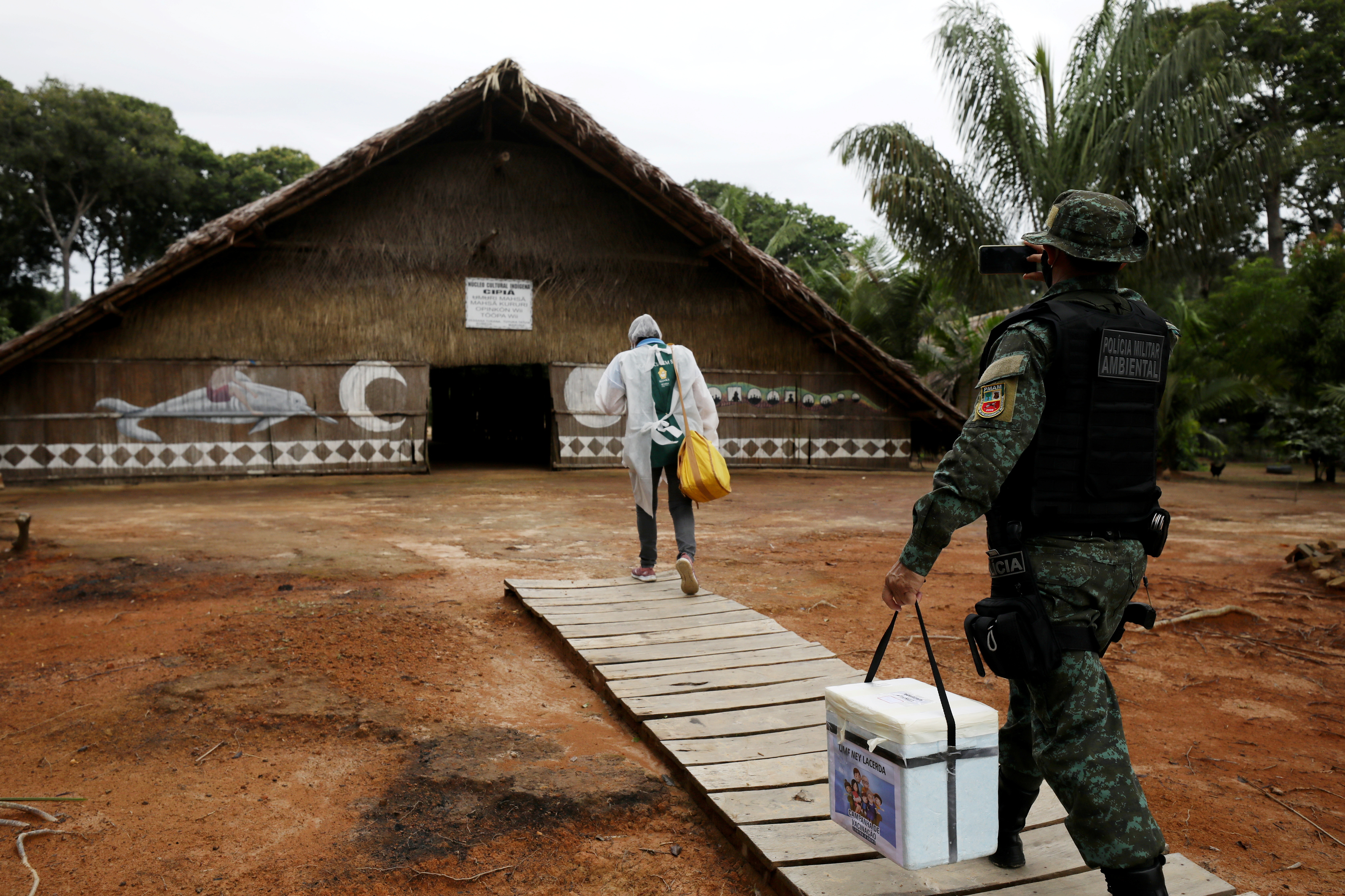A municipal health worker and an environmental military police officer carry the AstraZeneca/Oxford vaccine as they enter in an Indigenous hut at the the Sustainable Development Reserve of Tupe in the Negro river banks in Manaus, Brazil, February 9, 2021. Picture taken February 9, 2021. REUTERS/Bruno Kelly - RC2PPL92XUT5
