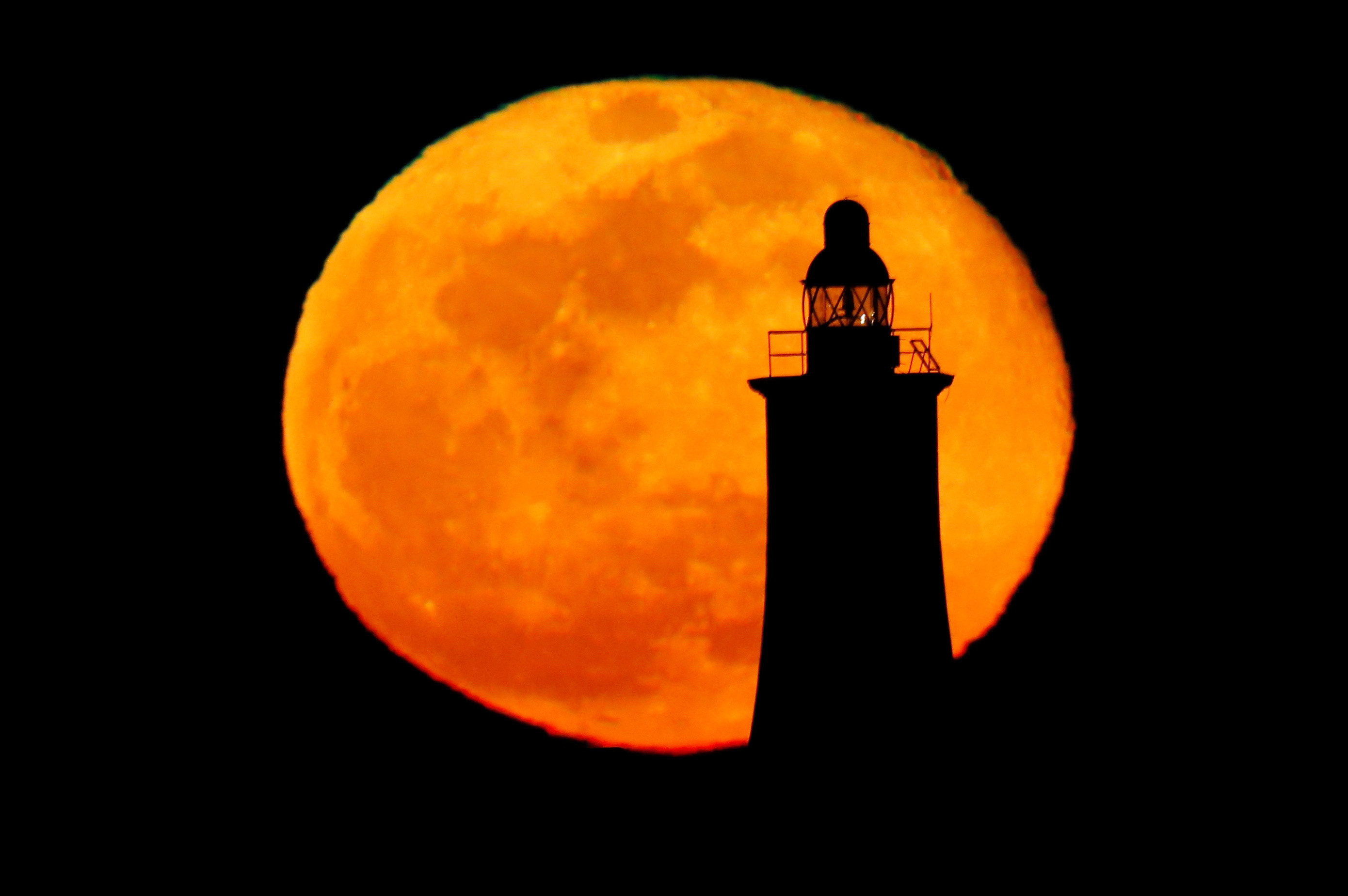 The pink supermoon, the biggest full moon of 2020, rises behind a lighthouse in Valletta, Malta April 8, 2020. REUTERS/Darrin Zammit Lupi - RC2I0G9MIUJM