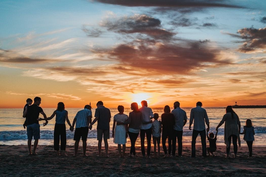 A number of people are standing next to each other on the beach, at sunset.