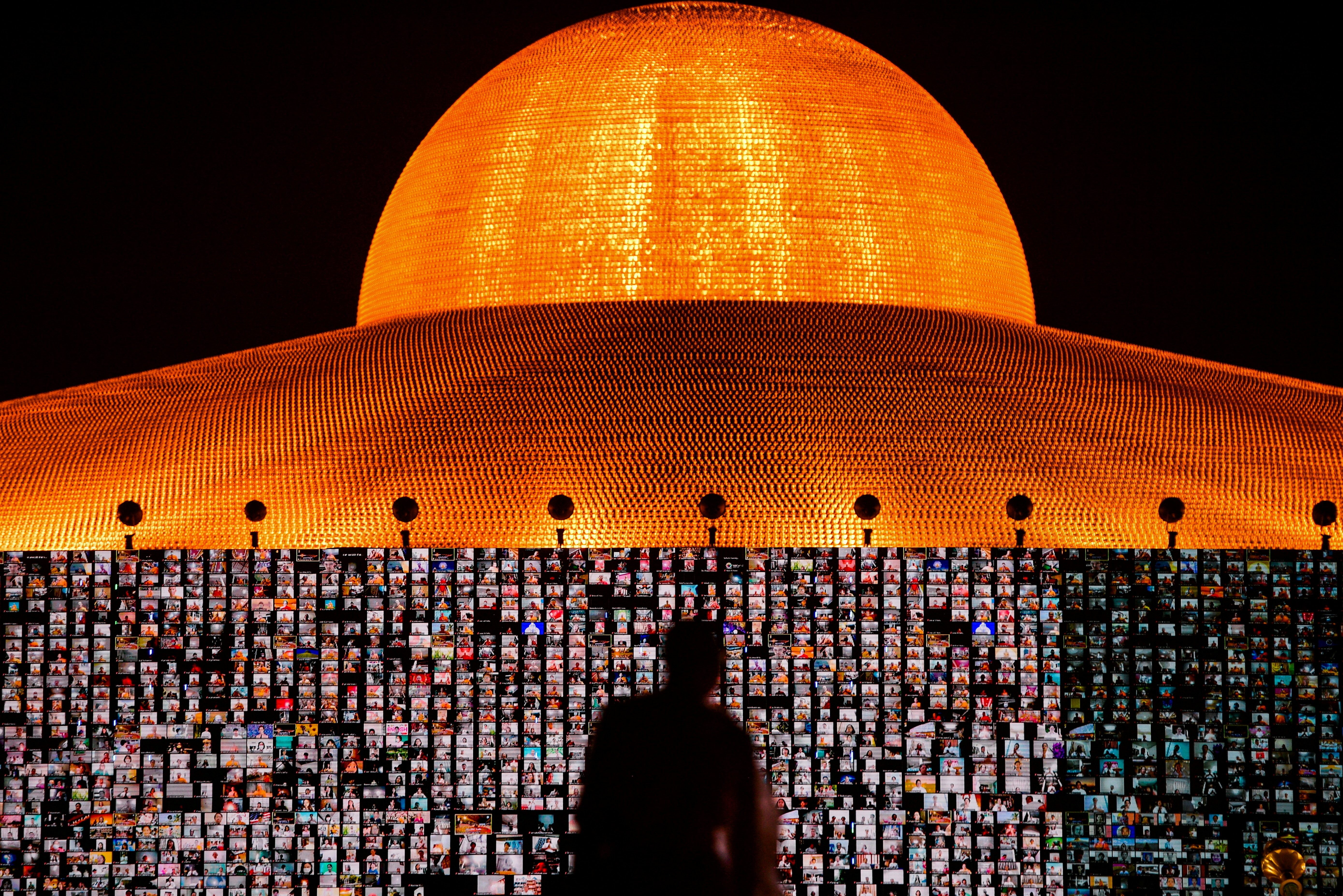 People pray as screens show devotees gathering via Zoom application during a ceremony to commemorate the Buddhist Lent Day at the Wat Phra Dhammakaya temple, amid the coronavirus disease (COVID-19) outbreaks, in Pathum Thani province, Thailand, July 24, 2021. REUTERS/Chalinee Thirasupa     TPX IMAGES OF THE DAY - RC2ZQO9KWXY2