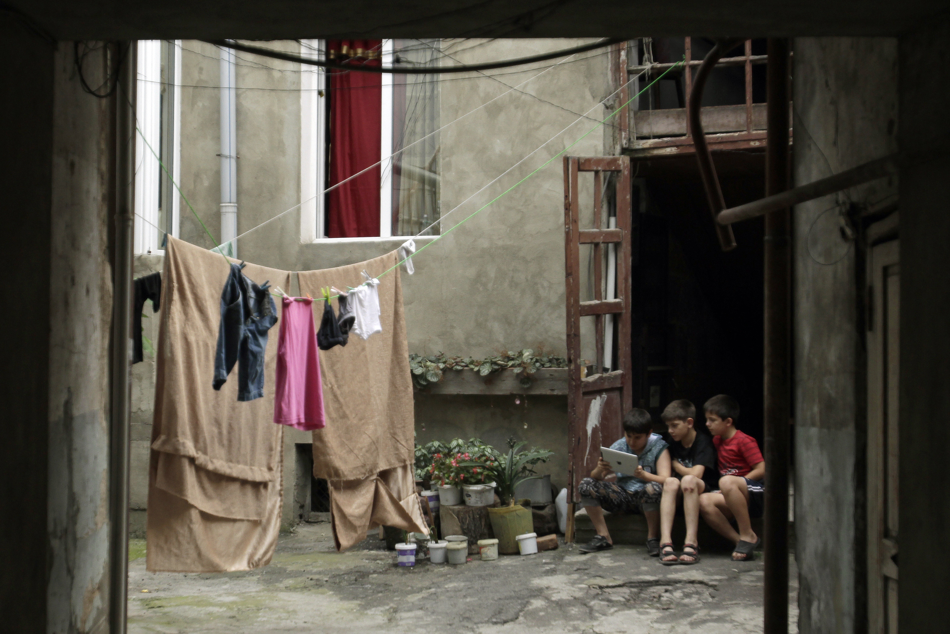 Children use an iPad as they sit in a courtyard in Tbilisi July 18, 2013. REUTERS/David Mdzinarishvili (GEORGIA - Tags: SOCIETY SCIENCE TECHNOLOGY) - GM1E97I1S2V01
