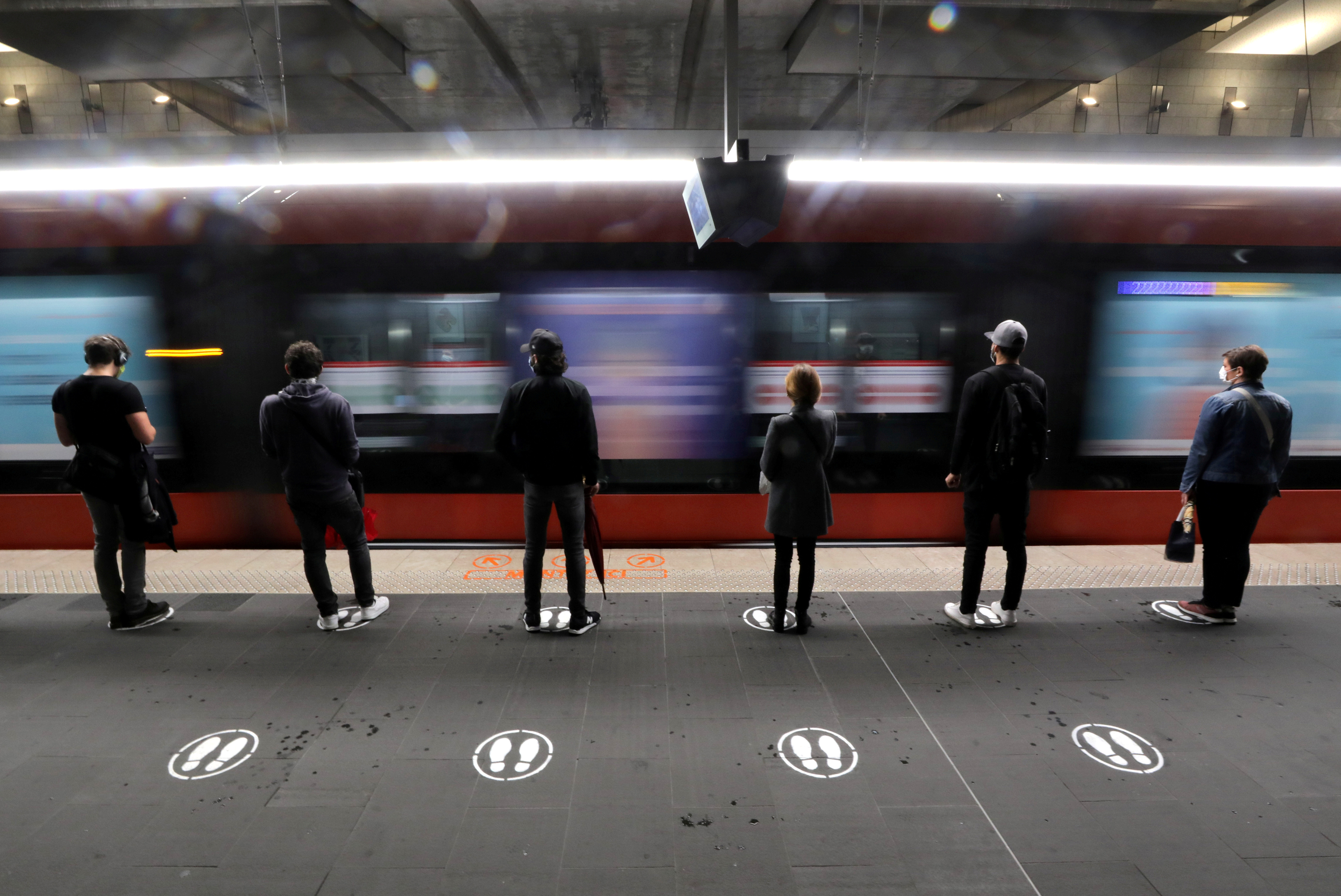 People stand on signs to respect social distancing on a platform for the tramway in Nice as France begun a gradual end to a nationwide lockdown due to the coronavirus disease (COVID-19), France, May 11, 2020.  REUTERS/Eric Gaillard     TPX IMAGES OF THE DAY - RC27MG9CYF7G