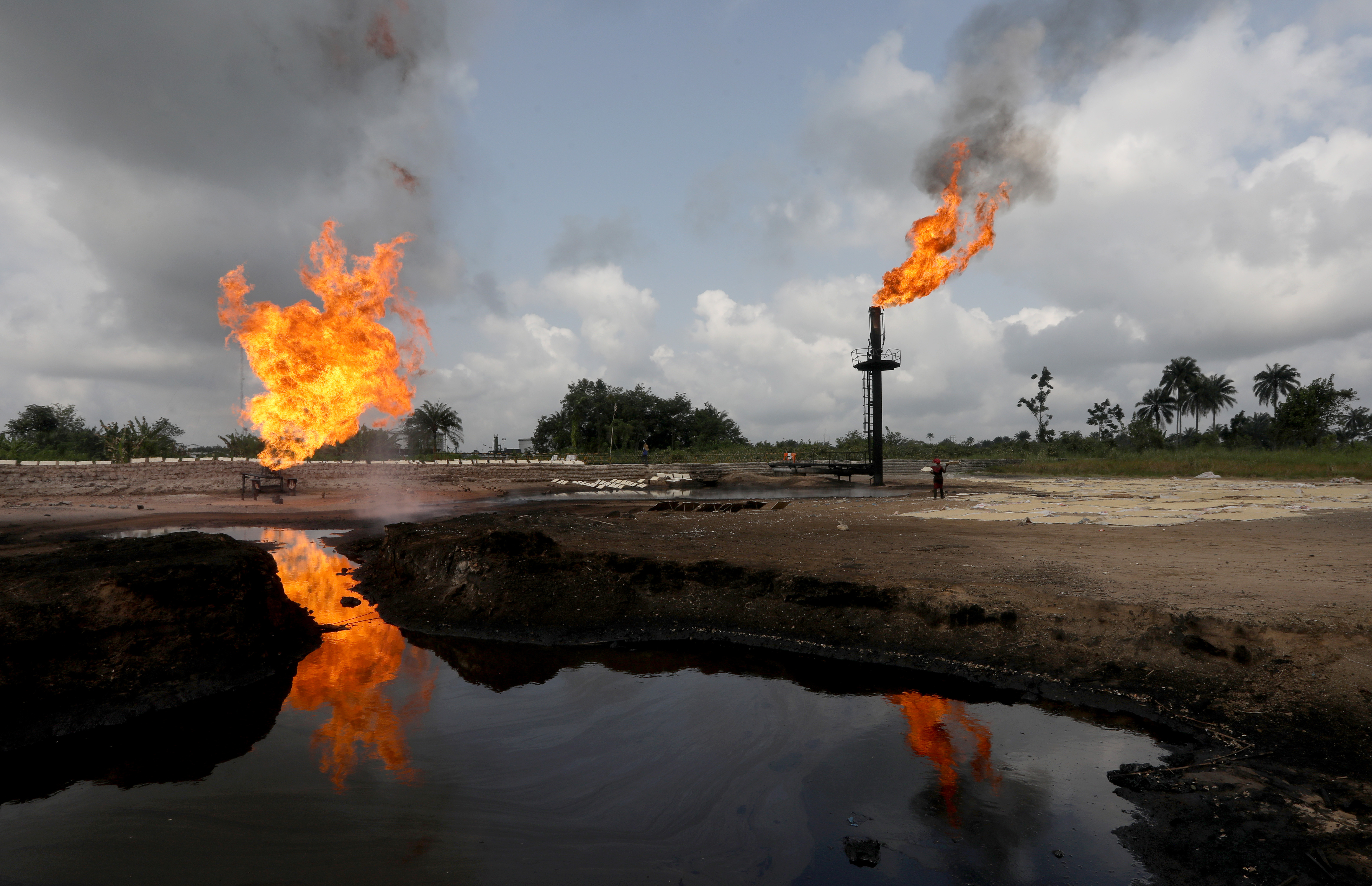 A reflection of two gas flaring furnaces is seen in the pool of oil-smeared water at a flow station in Ughelli, Delta State, Nigeria September 17, 2020. Picture taken September 17, 2020