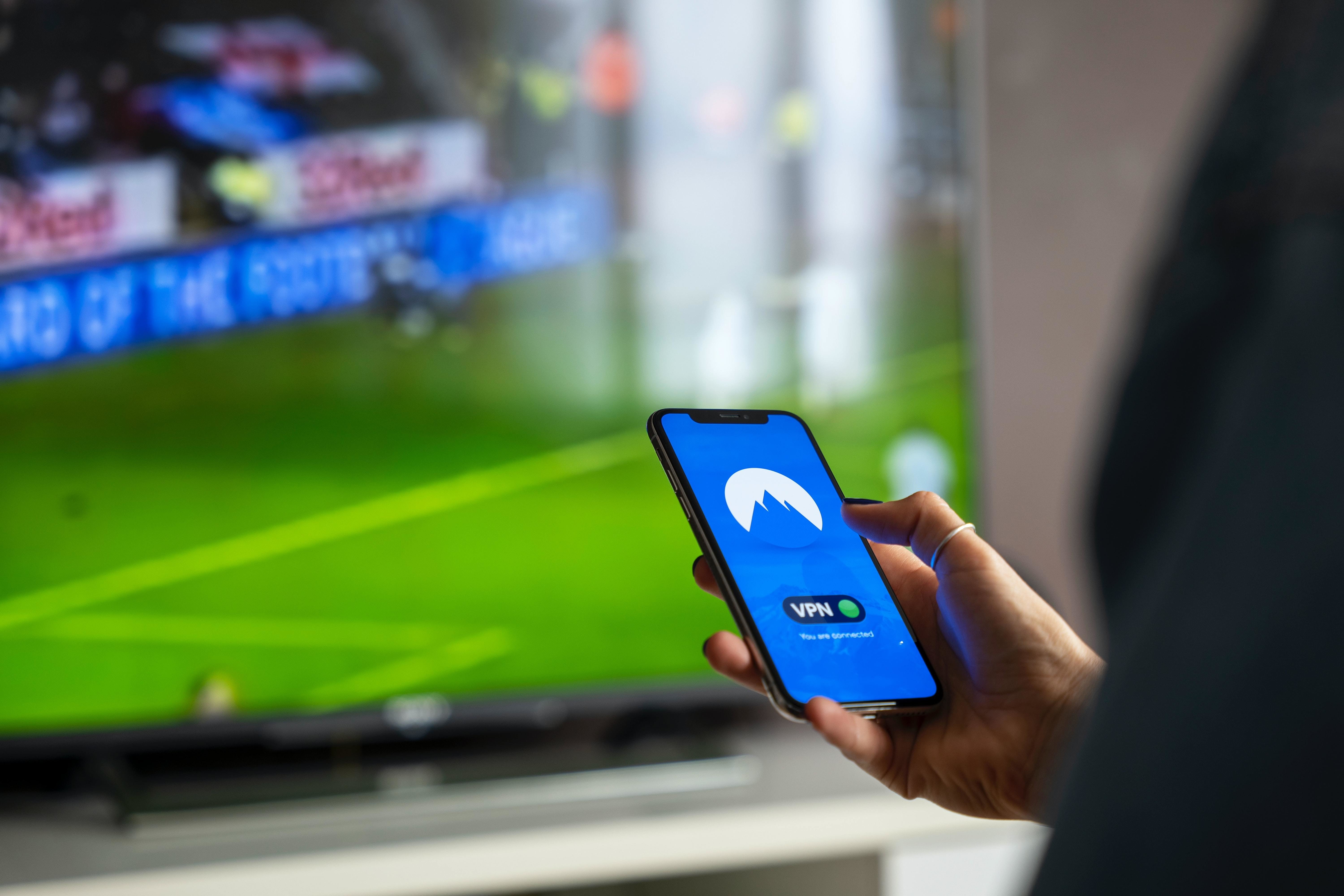 A person using a VPN on a mobile phone in front of a football game on a large TV screen.