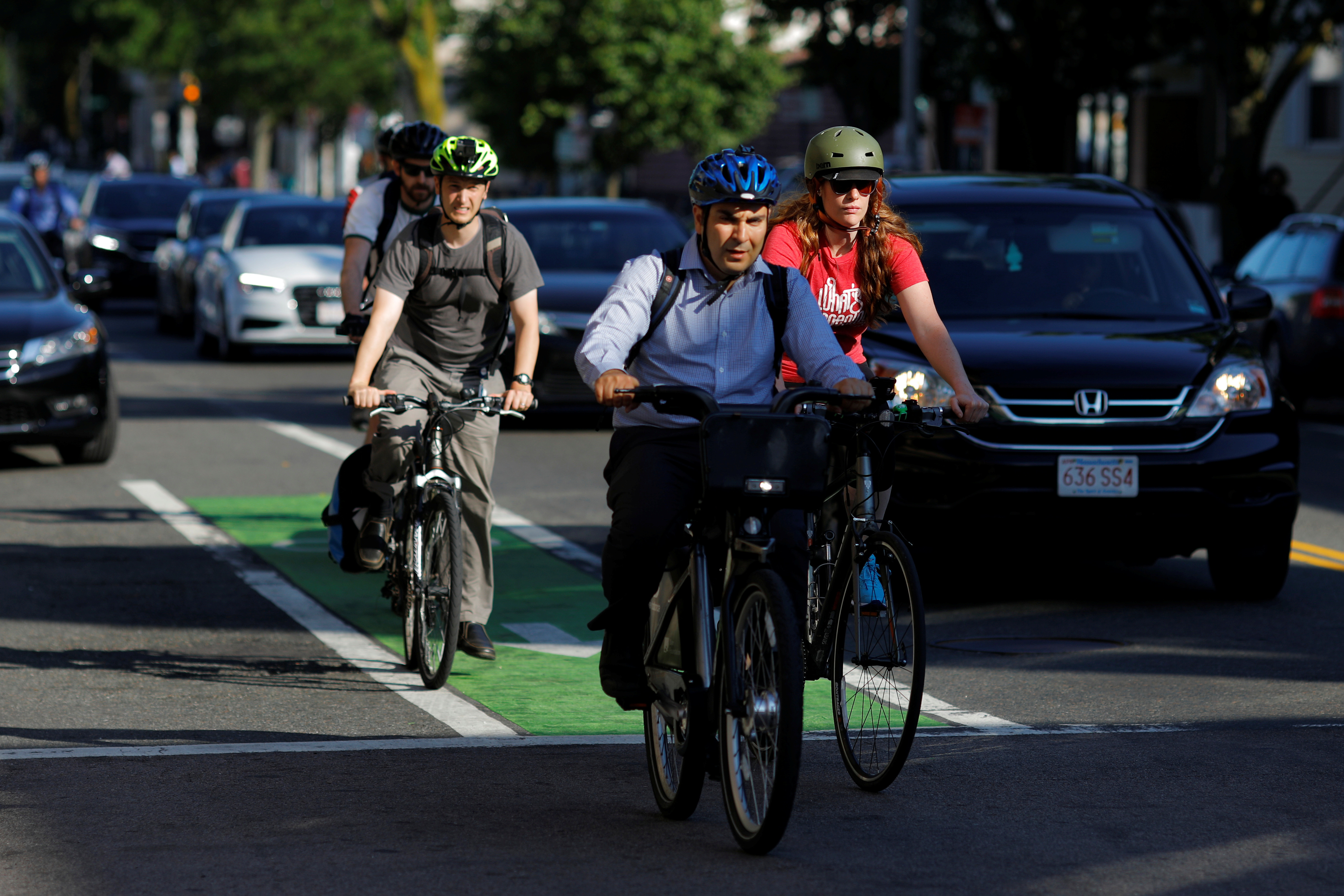 Cyclists and cars wait at a red light during the evening commute in Cambridge, Massachusetts, U.S., June 15, 2017.   REUTERS/Brian Snyder - RC150F6E5520