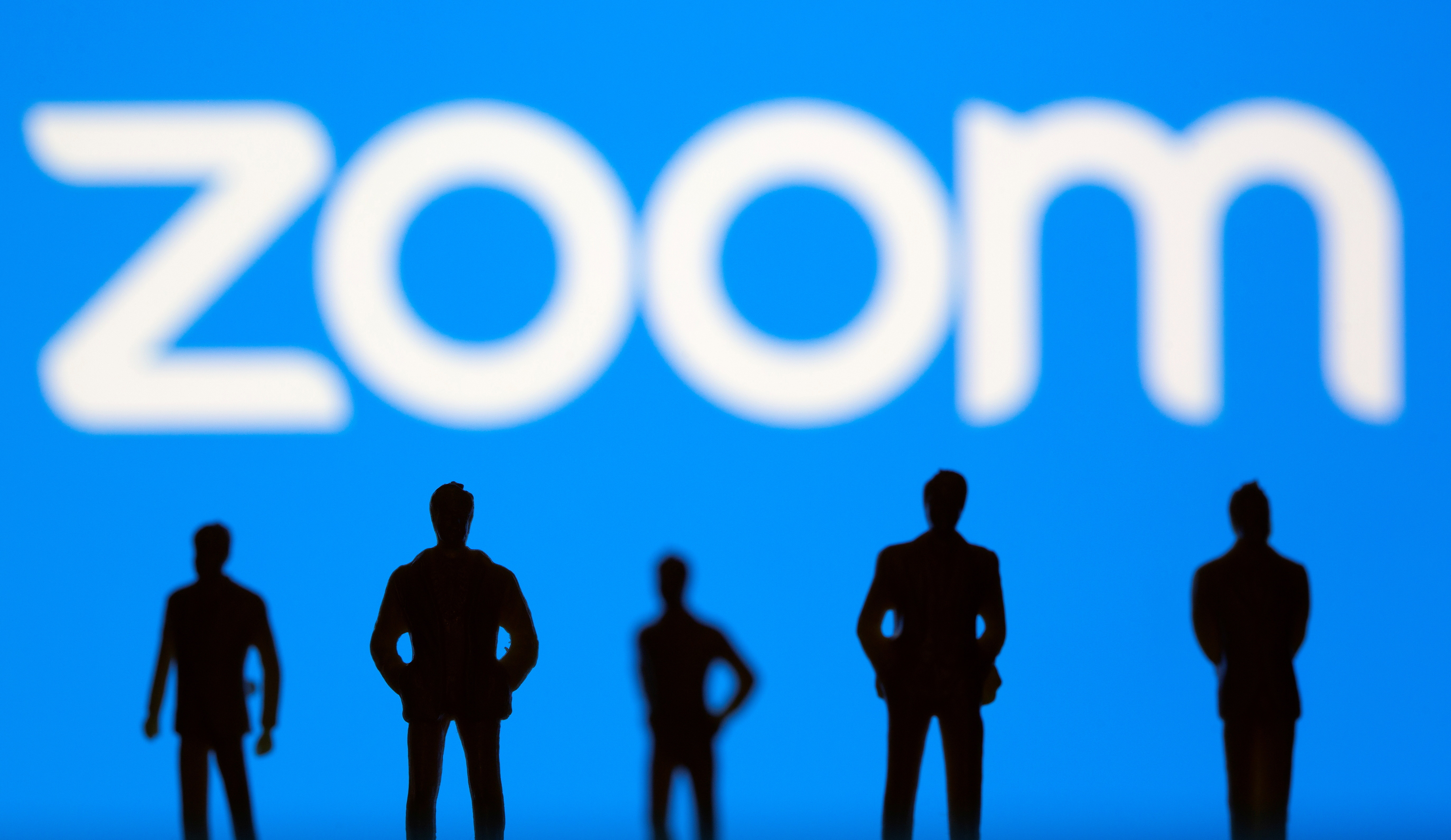 Small toy figures are seen in front of Zoom logo in this illustration picture taken March 15, 2021. REUTERS/Dado Ruvic/Illustration - RC2ICM9ZIWDV