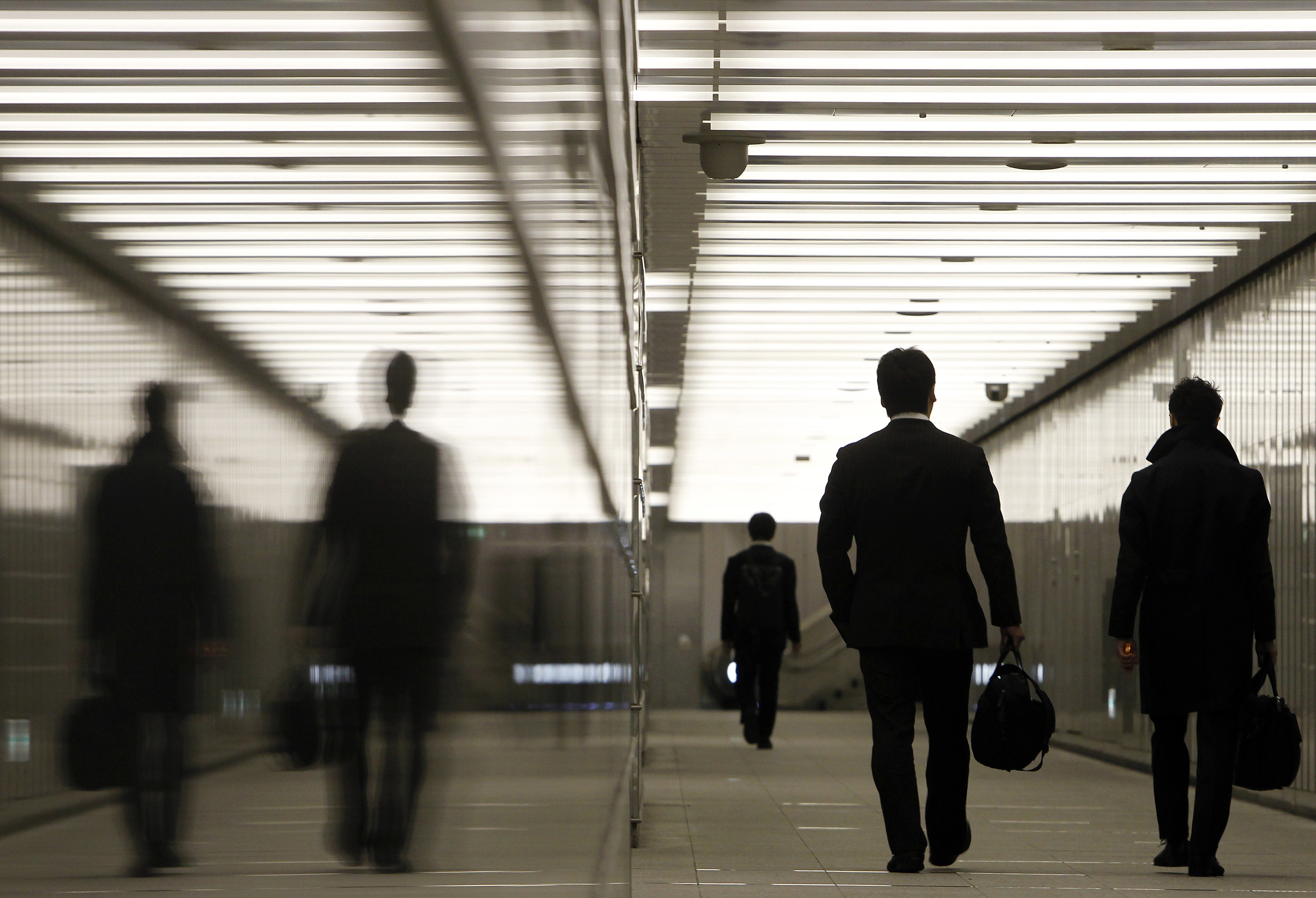 Businessmen walk through a business complex in Tokyo January 11, 2011. Japan's index of coincident economic indicators rose a preliminary 1.4 points in November from the previous month, the Cabinet Office said on Tuesday, up for the first time in three months. REUTERS/Yuriko Nakao (JAPAN - Tags: EMPLOYMENT BUSINESS POLITICS IMAGES OF THE DAY) - GM1E71B1CN001