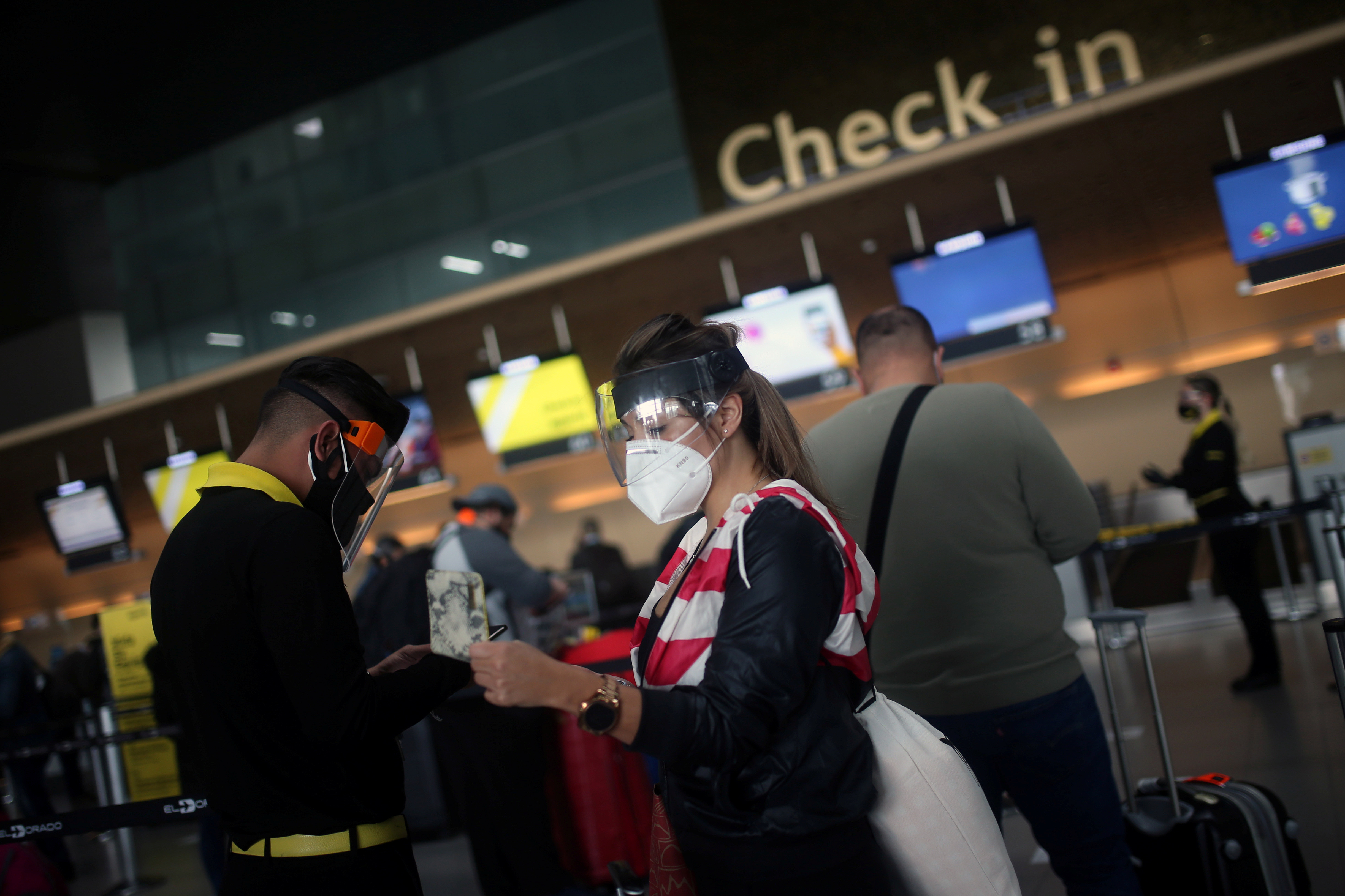 Passengers wearing face masks line up to check in at El Dorado airport, after the Colombian government gave the authorization to reactivate international flights, amidst the coronavirus disease (COVID-19) outbreak, in Bogota, Colombia September 21, 2020. REUTERS/Luisa Gonzalez - RC253J9KGO28