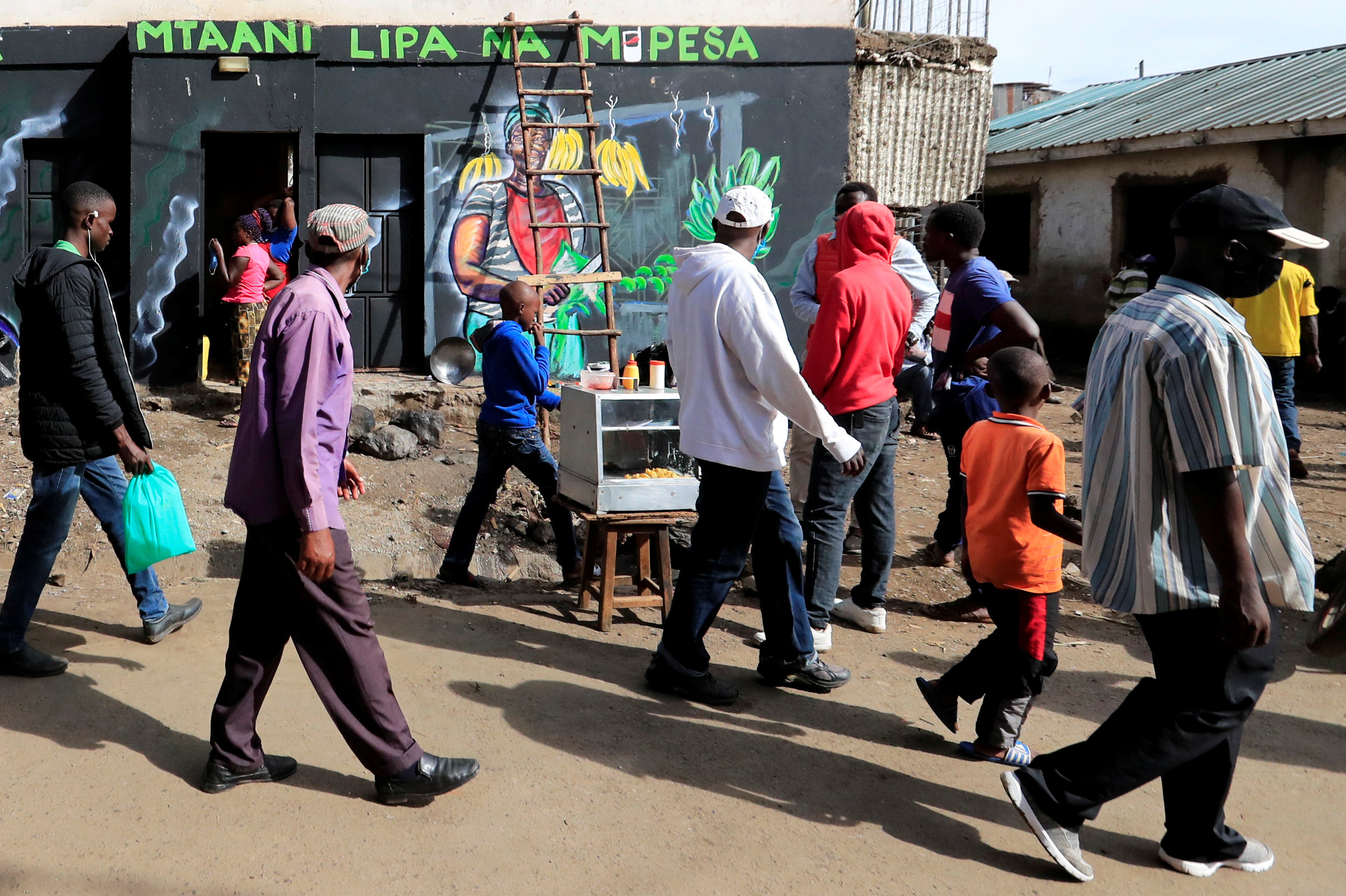 Residents walk past a mural advocating for retail M-Pesa mobile phone cashless payments as a measure against the spread of the coronavirus disease (COVID-19) in Nairobi, Kenya April 19, 2020. Picture taken April 19, 2020. REUTERS/Thomas Mukoya - RC288G9RF2H1