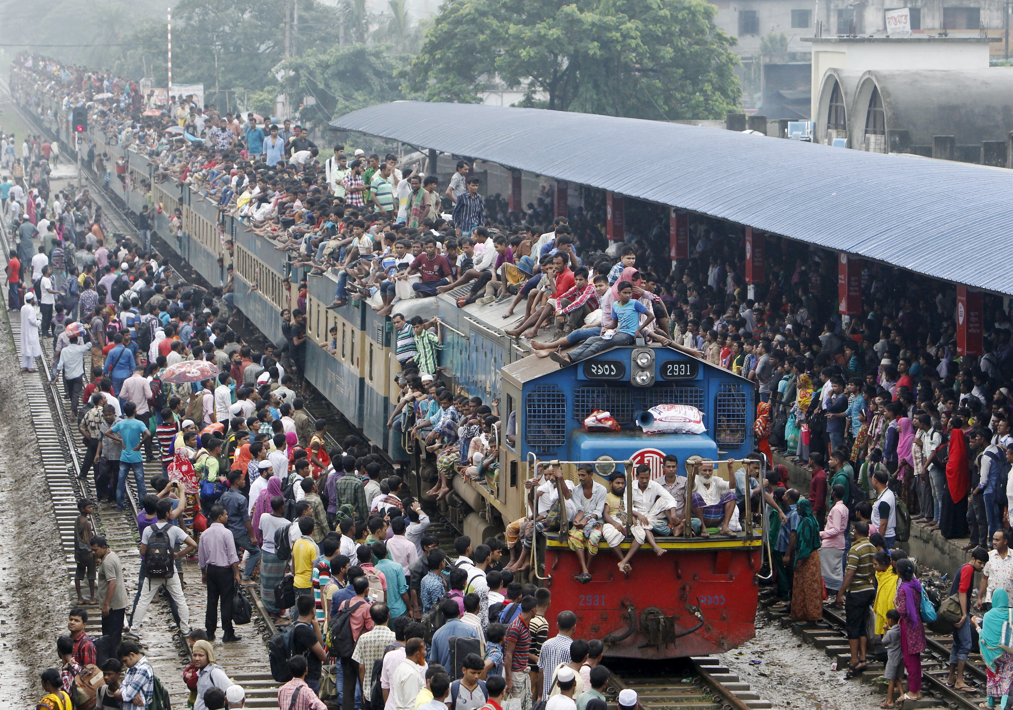 People crowd on top of a train entering the Dhaka airport rail station September 24, 2015, as thousands of Bangladeshi Muslims head home to celebrate Eid-al-Adha. Muslims across the world are celebrating the annual festival of Eid al-Adha also known as the Feast of the Sacrifice. REUTERS/Ashikur Rahman      TPX IMAGES OF THE DAY      - GF10000218305
