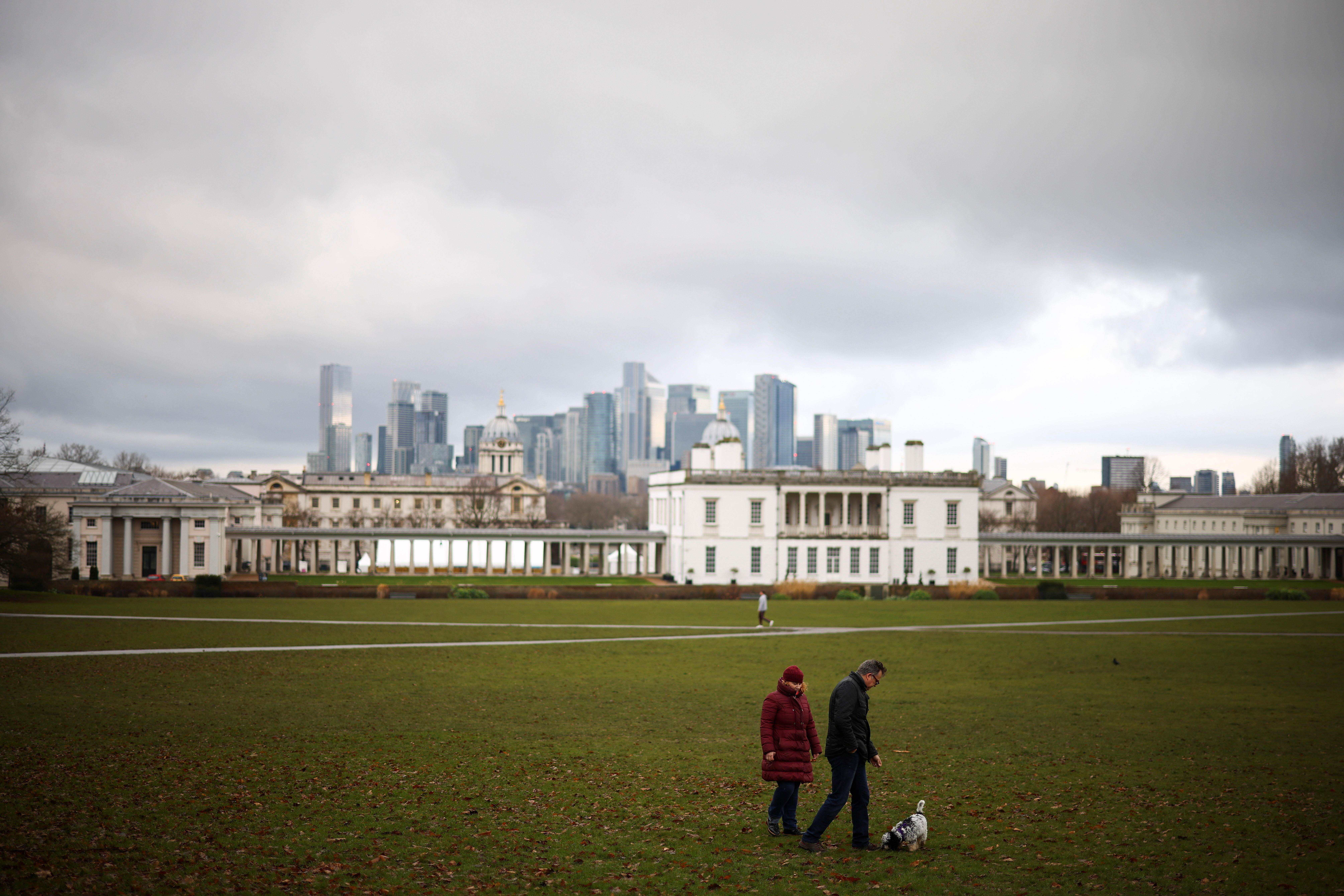People walk their dog in Greenwich park