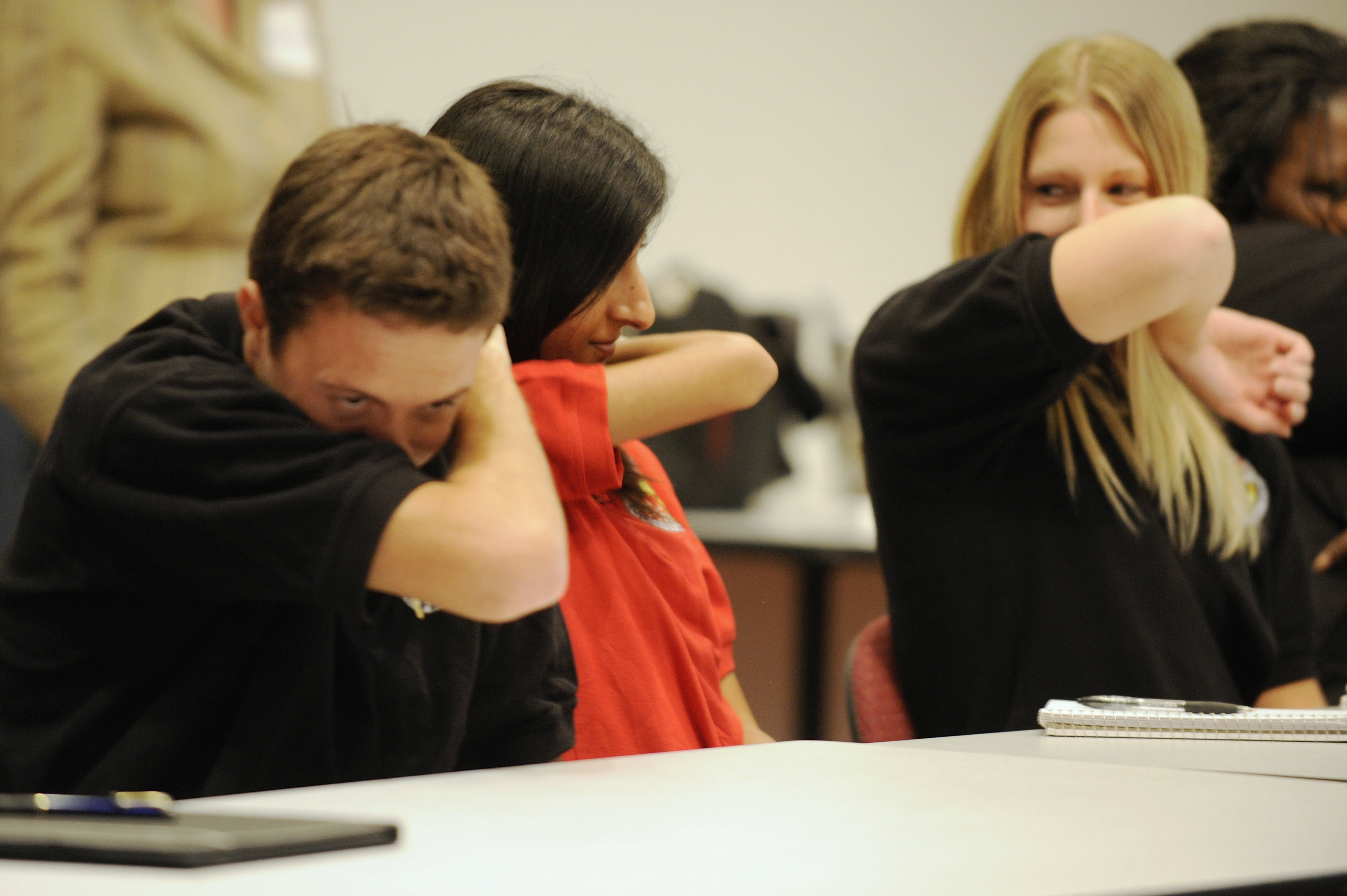 People practice coughing into their sleeves as a way to try to control the spread of the H1N1 swine flu virus, during a meeting for workers at the Maryland Department of Health and Mental Hygiene in Baltimore, September 3, 2009. The new H1N1 virus has killed 36 U.S. children, the U.S. Centers for Disease Control and Prevention reported on Thursday.   REUTERS/Jonathan Ernst    (UNITED STATES HEALTH) - GM1E5940AL301