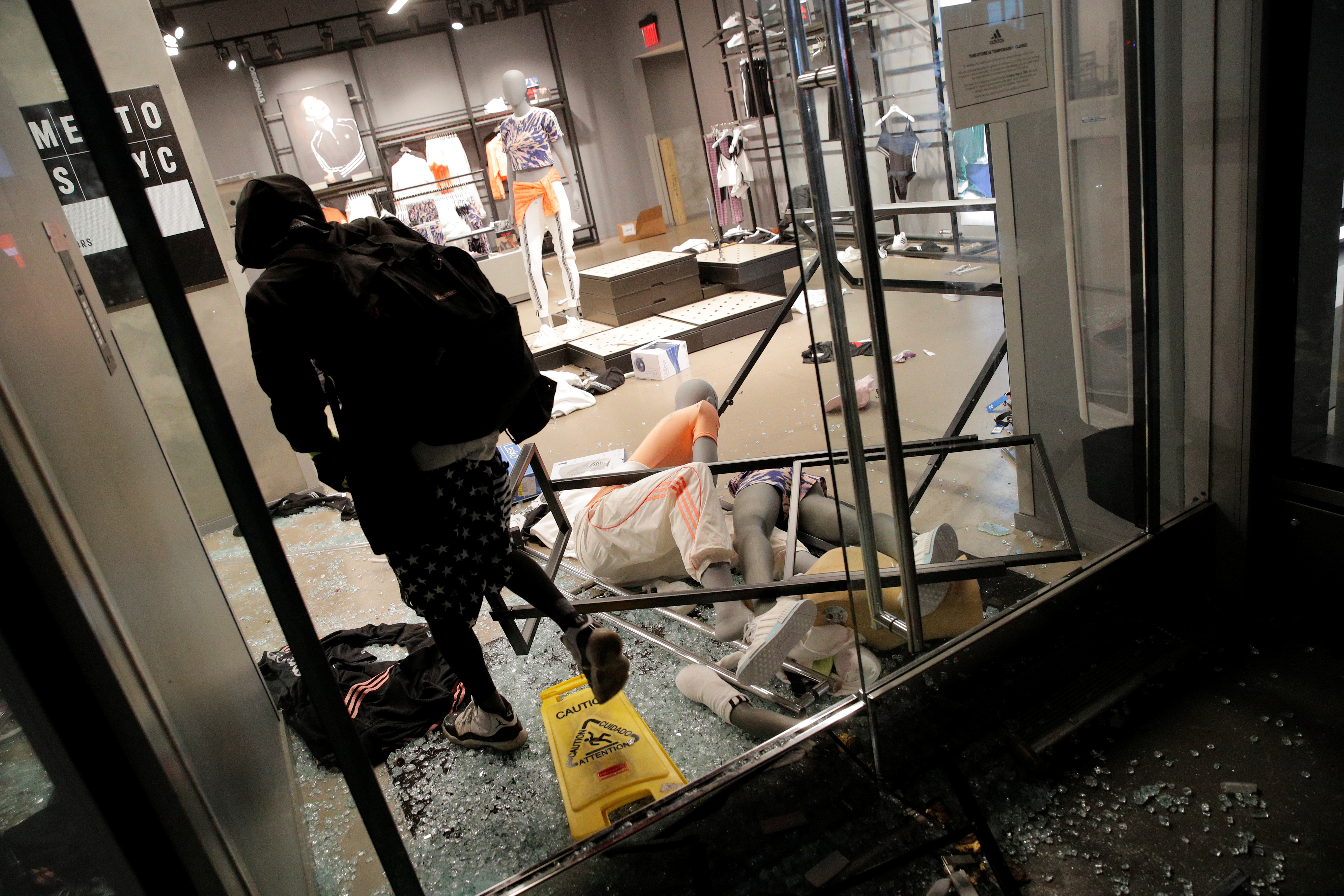 A person walks inside a damaged shop during a protest against the death in Minneapolis police custody of George Floyd, in Manhattan, New York, U.S., May 30, 2020. REUTERS/Andrew Kelly - RC2FZG94PL81