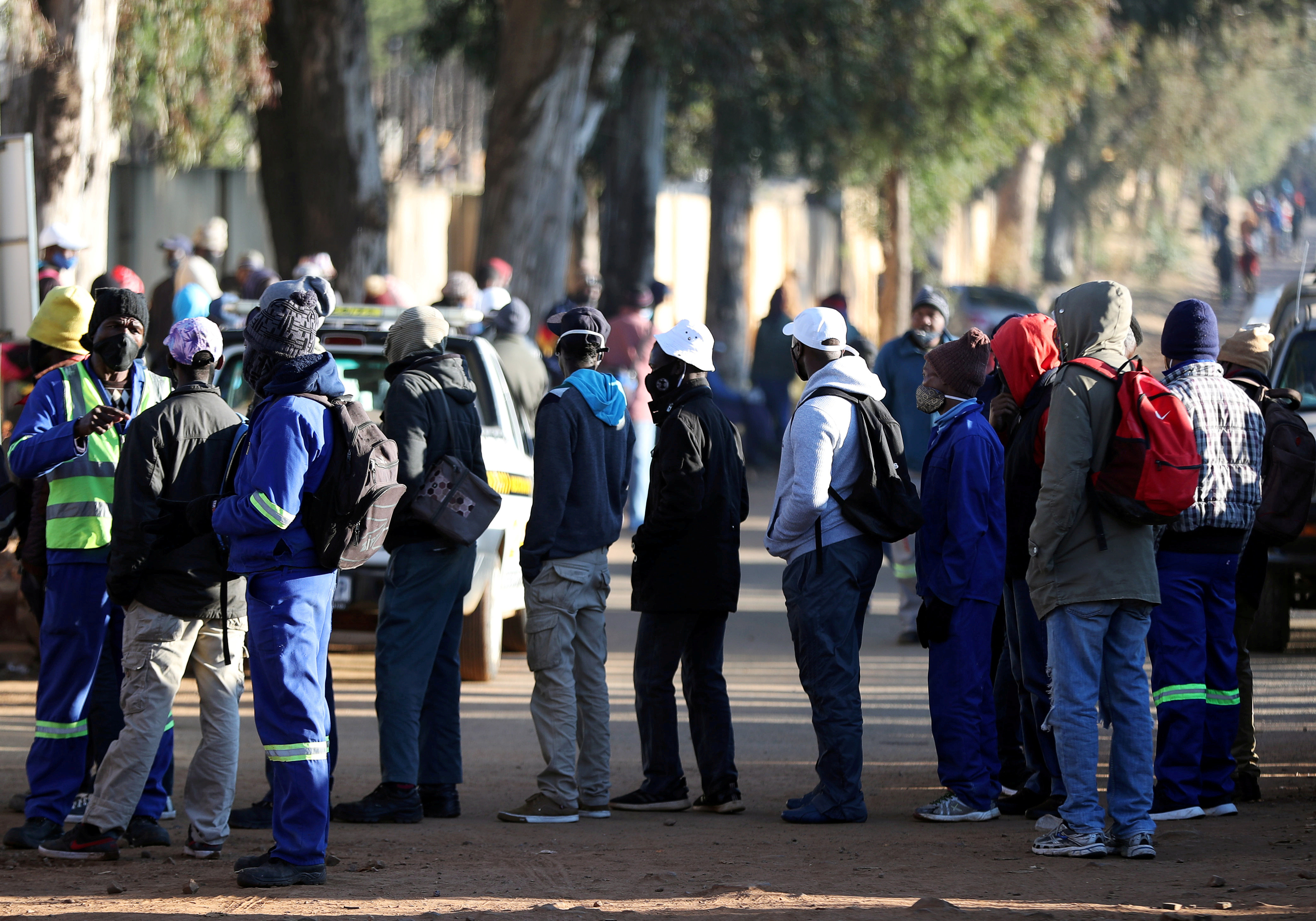 Job seekers stand outside a construction site ahead of the release of the unemployement numbers by Statistics South Africa, in Eikenhof, south of Johannesburg, South Africa, June 23, 2020. REUTERS/Siphiwe Sibeko - RC2VEH9YEZV1