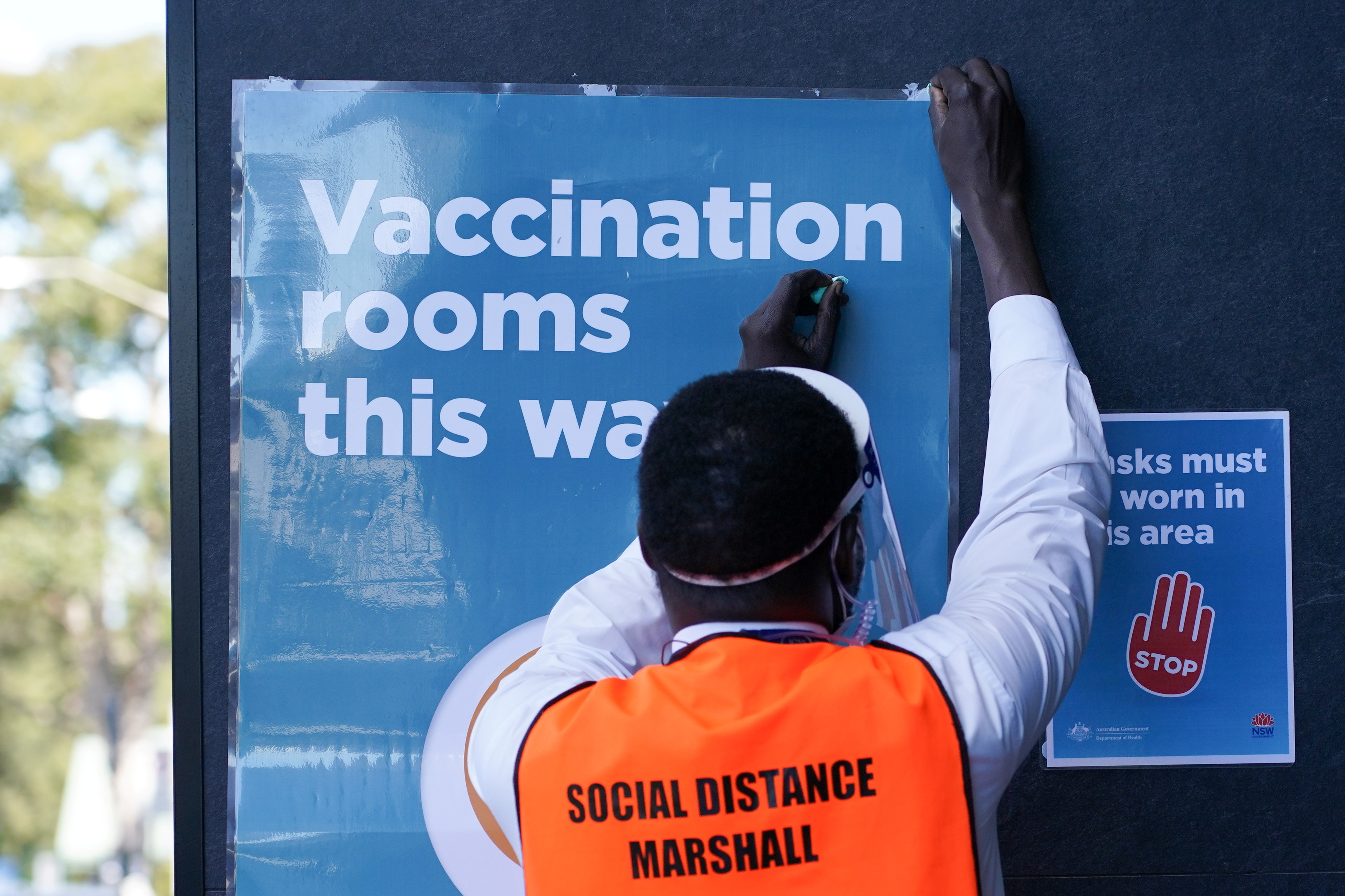 A staff member straightens a sign outside a coronavirus disease (COVID-19) vaccination clinic at the Bankstown Sports Club as the city experiences an extended lockdown, in Sydney, Australia, August 3, 2021.  REUTERS/Loren Elliott - RC2EXO9LXBD1