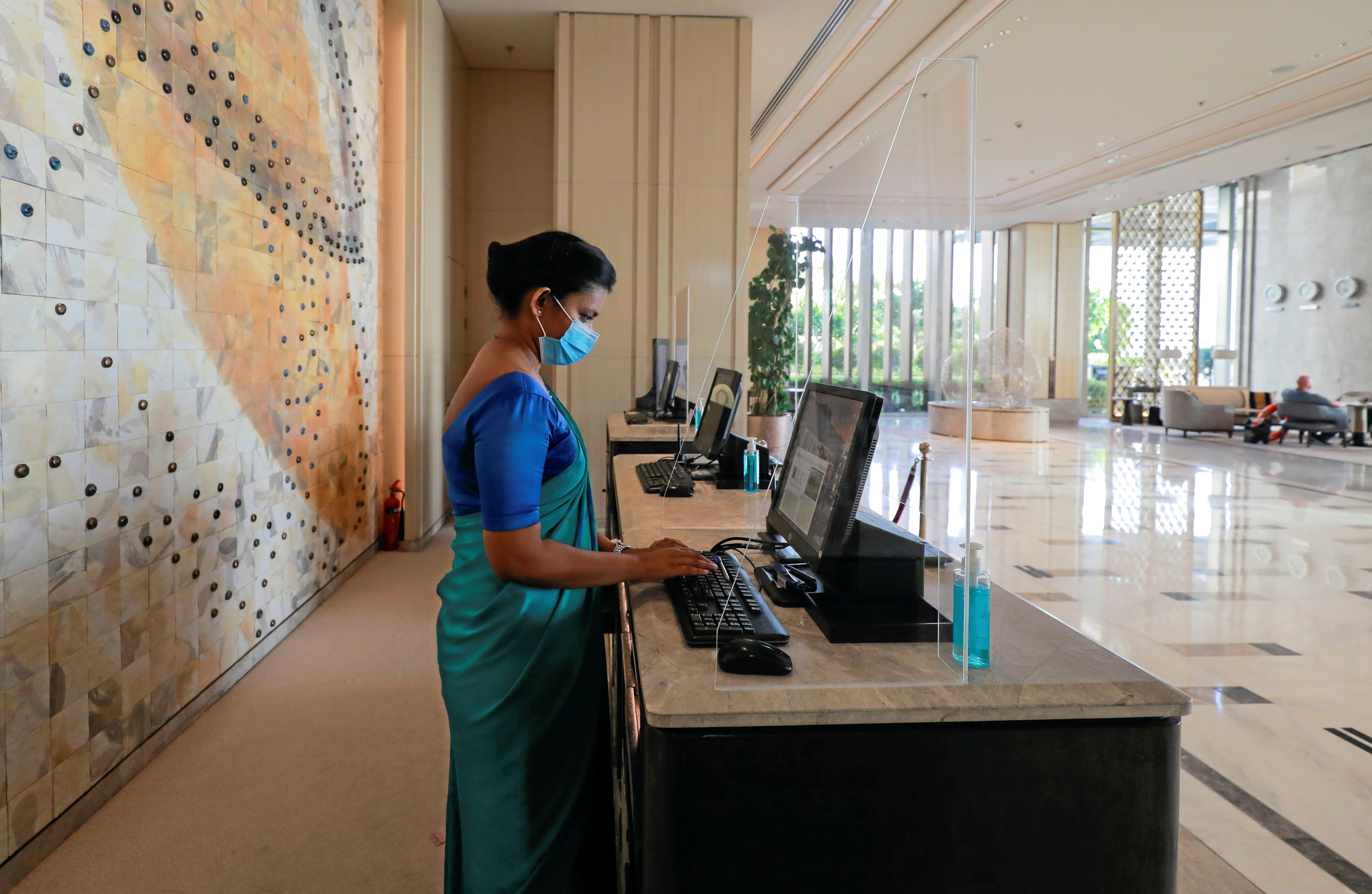 A receptionist wearing a protective mask is seen behind a protective screen at the main entrance of the Shangri-La hotel, amid concerns about the spread of the coronavirus disease (COVID-19), in Colombo, Sri Lanka, July 1, 2020. REUTERS/Dinuka Liyanawatte - RC2EKH98LCDQ
