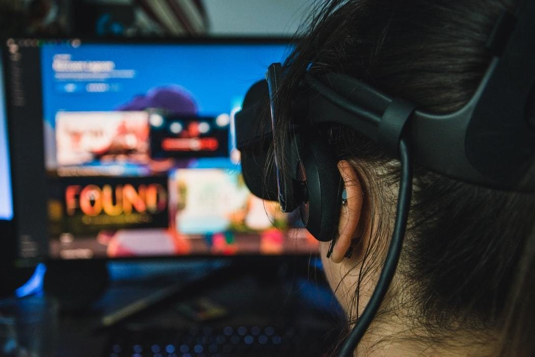 A woman wears a headset as she explores a virtual world.