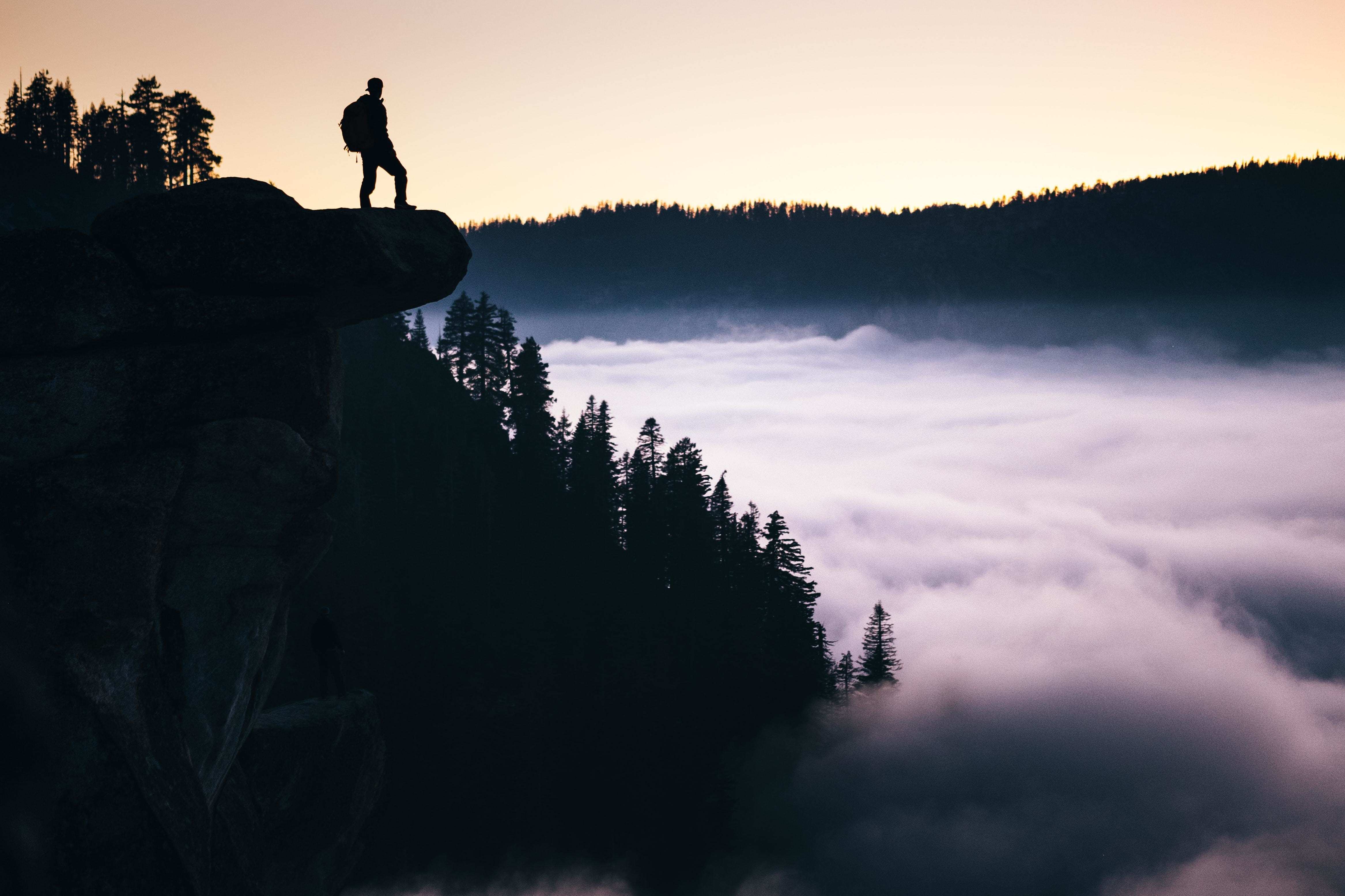 Person on cliff, forest, mist, sunset; tipping points for sustainable investment
