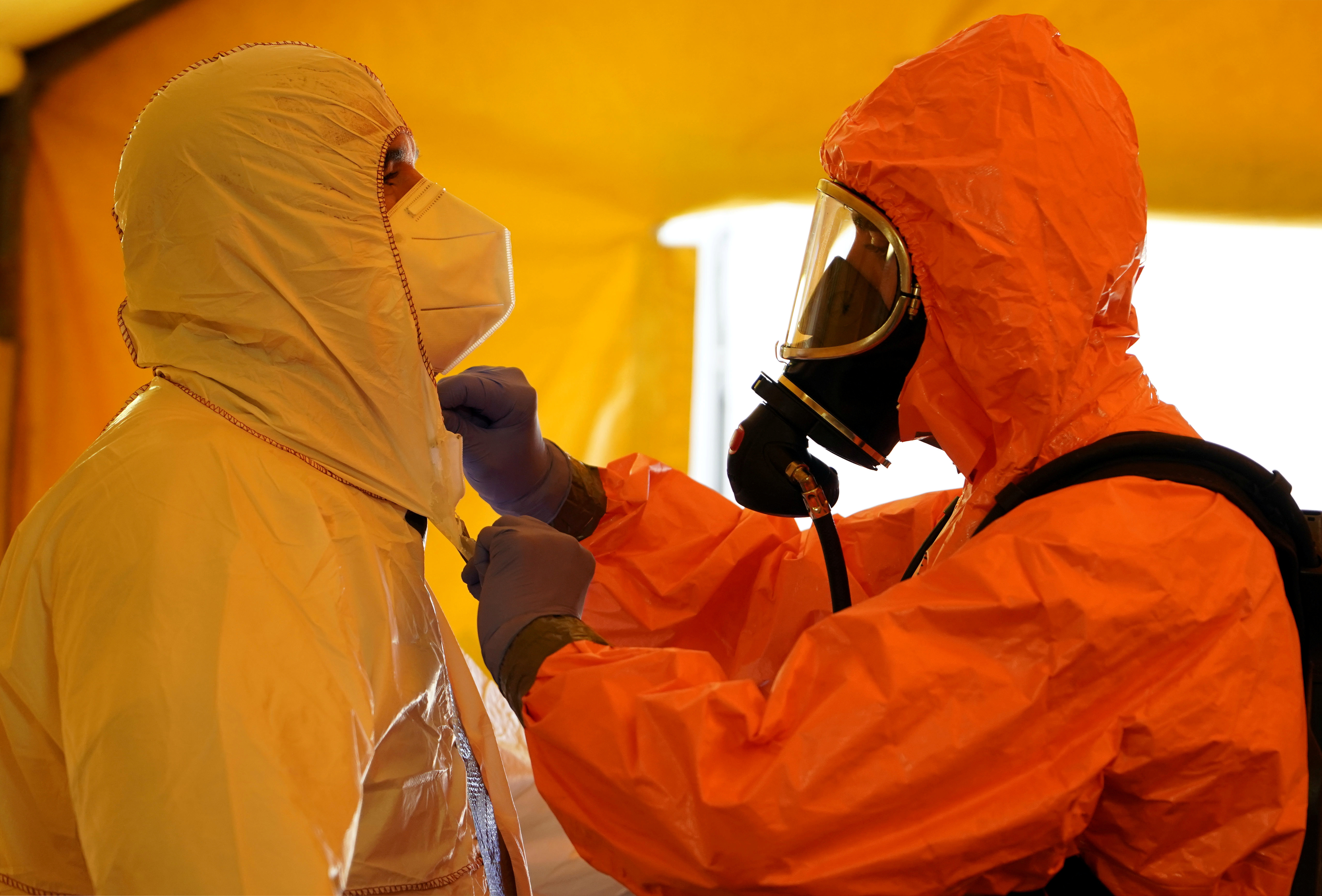 A member of Madrid's SAMUR Ambulance Service adjusts protective gear of his colleague, during the coronavirus disease (COVID-19) pandemic, at their headquarters in Madrid, Spain, August 26, 2020. Picture taken August 26, 2020. REUTERS/Juan Medina - RC28MI929BW8