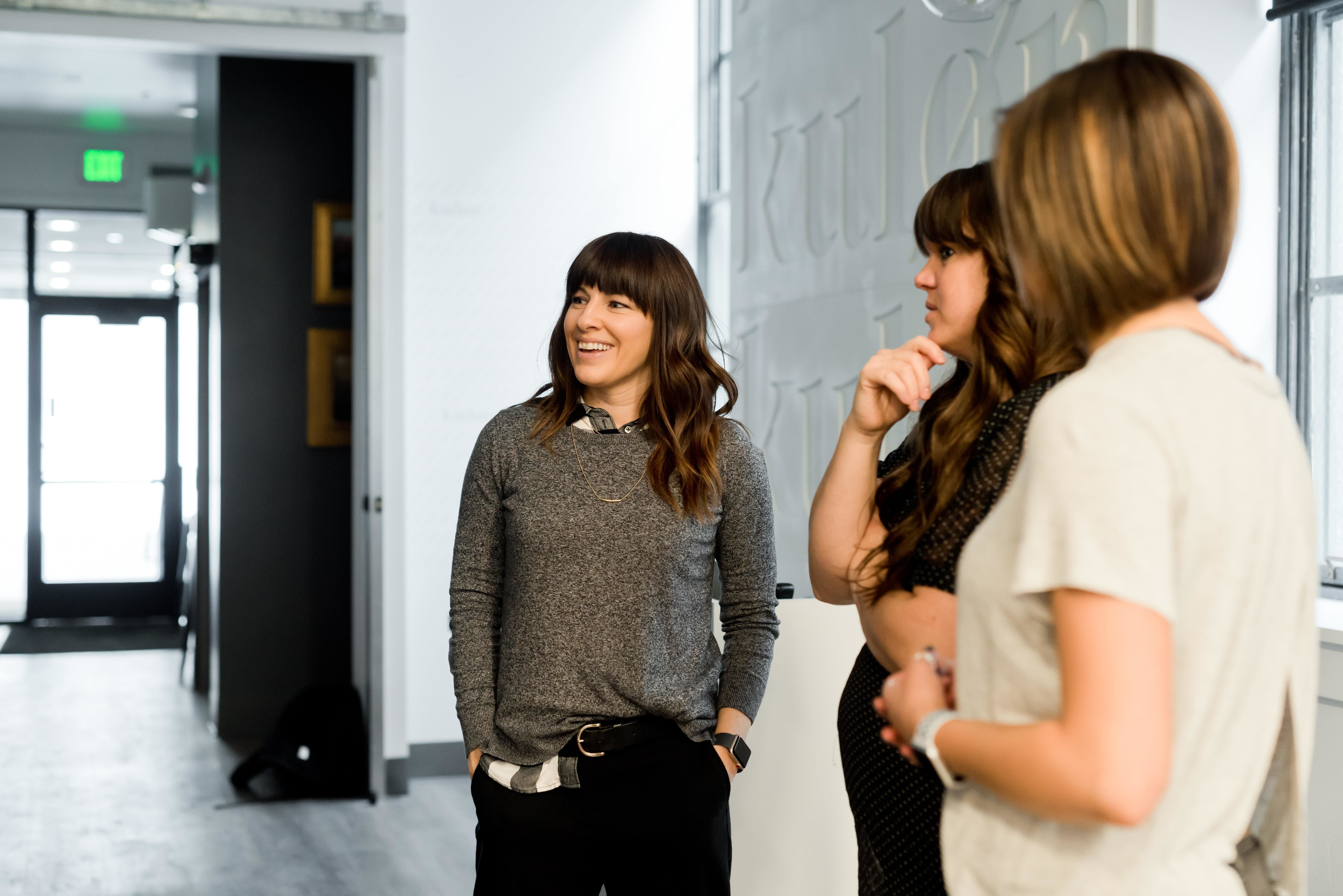 a picture of women in casual business dress talking among each other