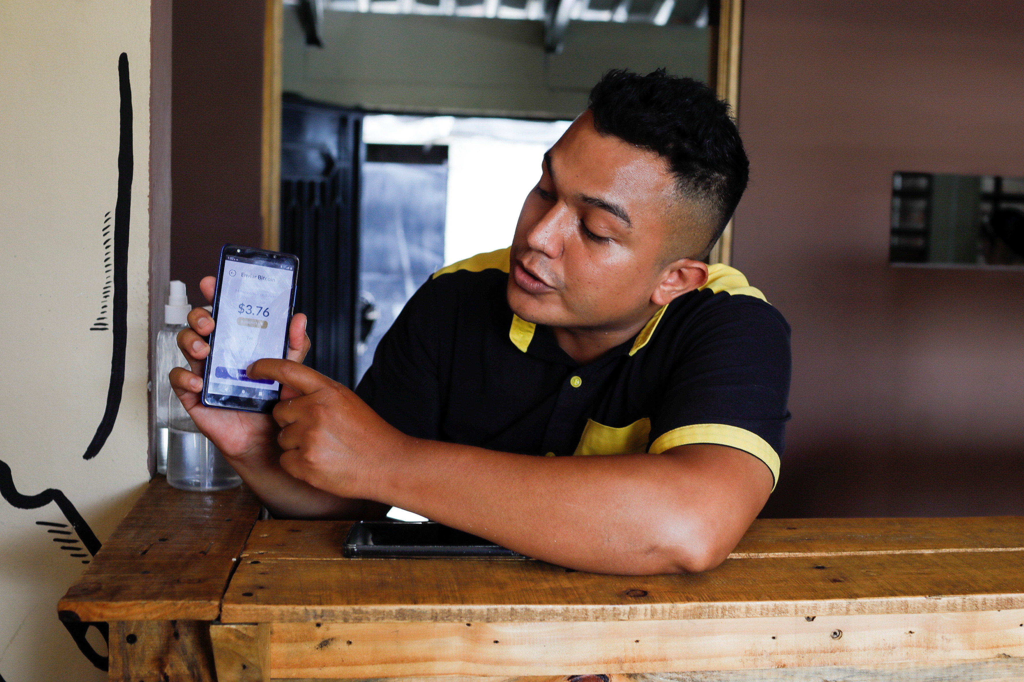 Alejandro Martinez, owner of Perronas Pizzas, helps a customer to pay for her order with a Bitcoin wallet that the Salvadoran government is launching for the use of Bitcoin as a legal tender, in Apopa, El Salvador