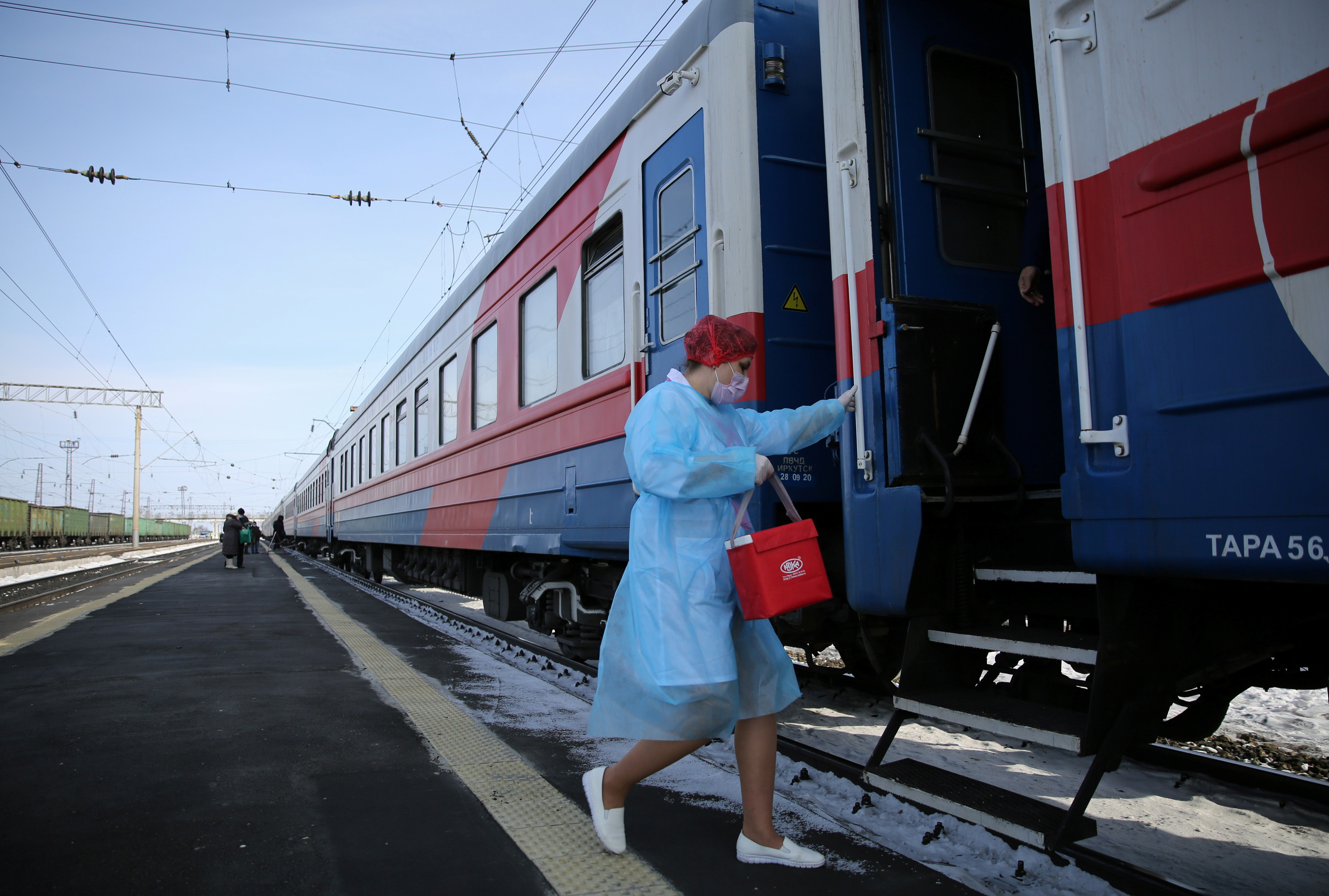 A medical worker carries a bag containing doses of the Sputnik V (Gam-COVID-Vac) vaccine against the coronavirus disease (COVID-19) as she enters a carriage of the Academician Fyodor Uglovmedical train, at a railway station in the town of Tulun in Irkutsk Region, Russia March 16, 2021. REUTERS/Evgeny Kozyrev - RC2GCM96JYV1