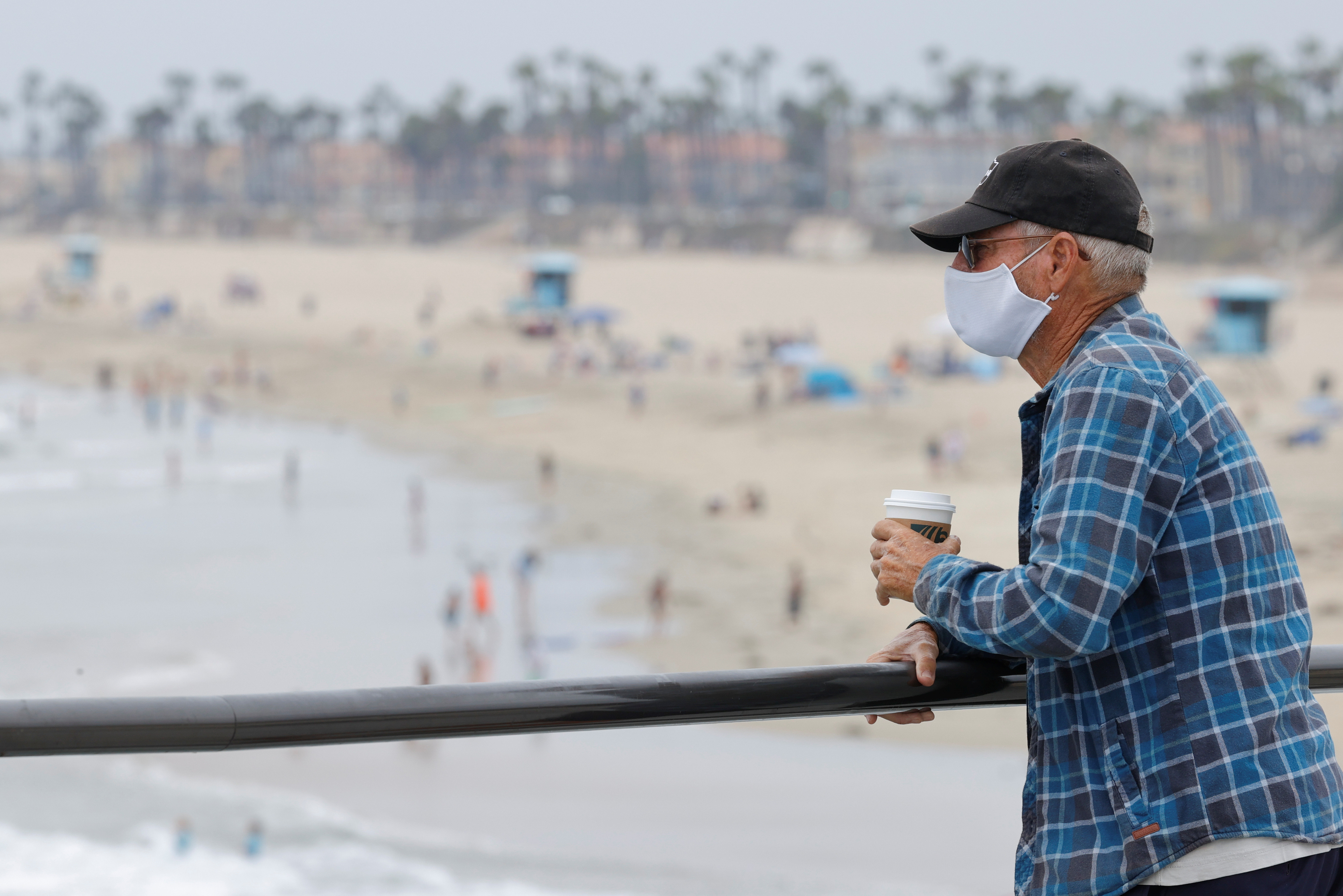 A man wearing a face mask looks out at the beach as the United States on Thursday passed a total of more than 4 million coronavirus infections during the global outbreak of the coronavirus disease (COVID-19) in Huntington Beach, California, U.S., July 23, 2020. REUTERS/Mike Blake - RC2AZH96X12I