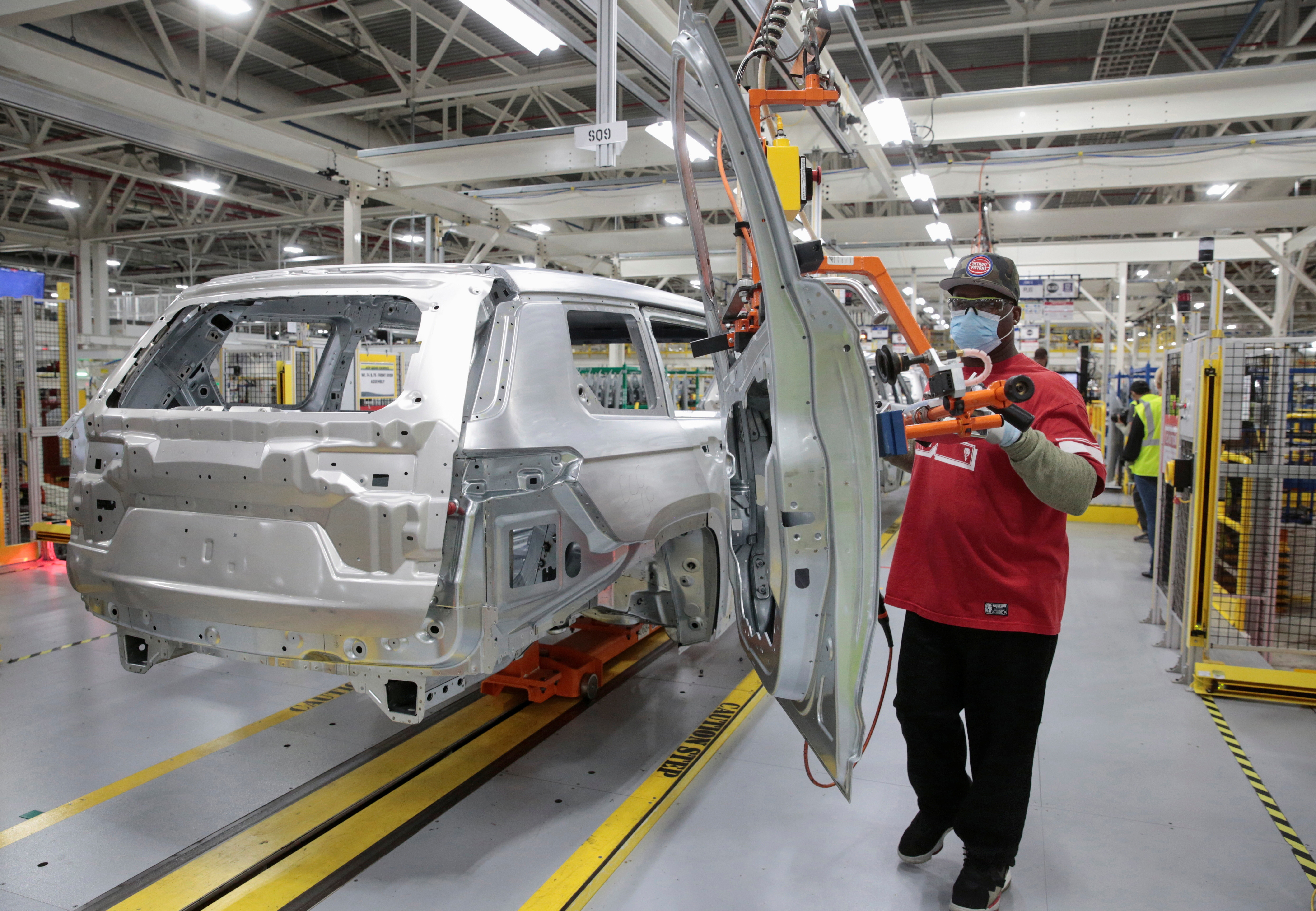 a worker assembles a car in a factory