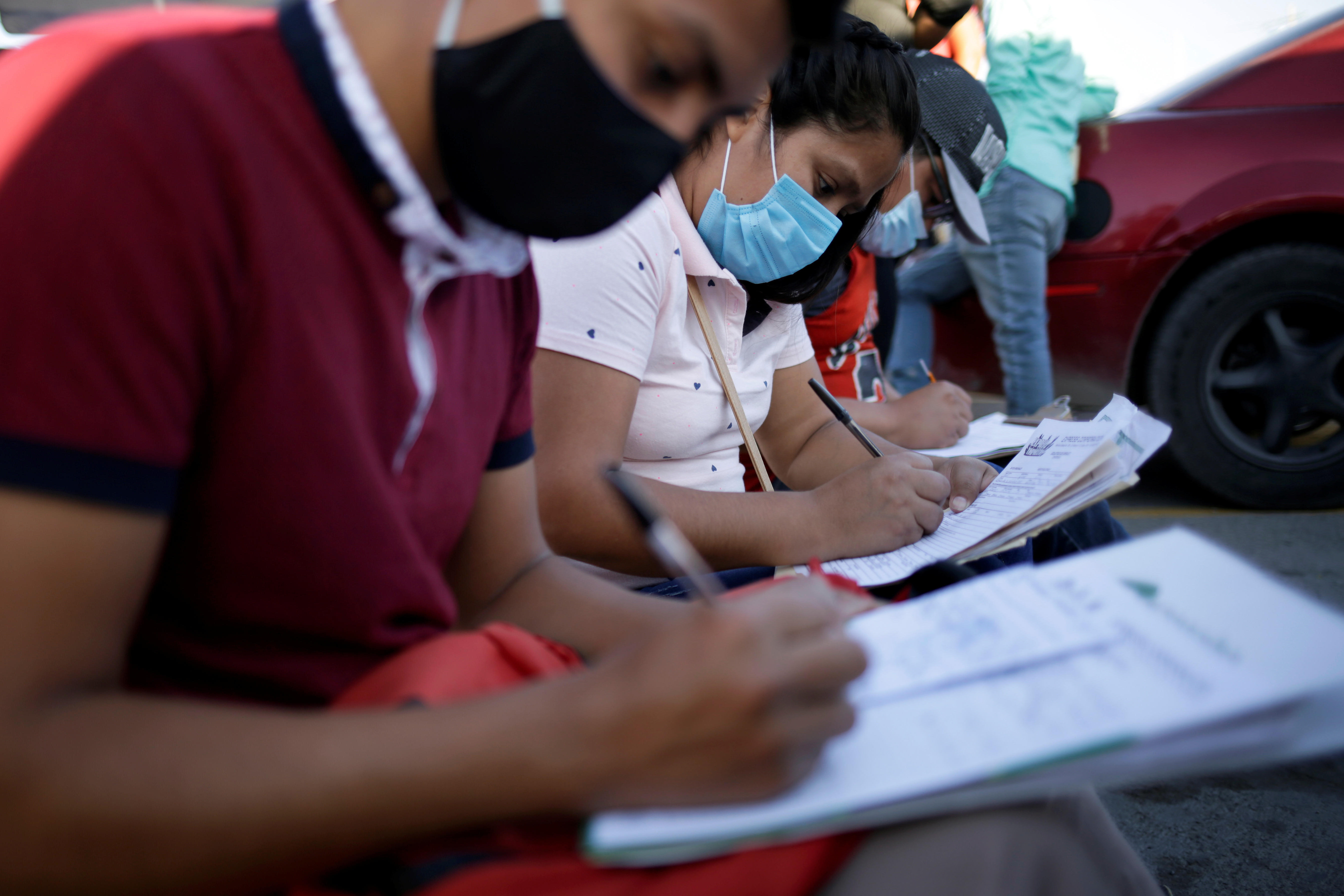 Job seekers fill out job application forms for assembly factories as the coronavirus disease (COVID-19) outbreak continues in Ciudad Juarez, Mexico June 17, 2020. Picture taken June 17, 2020. REUTERS/Jose Luis Gonzalez - RC2VJH9DJJPC