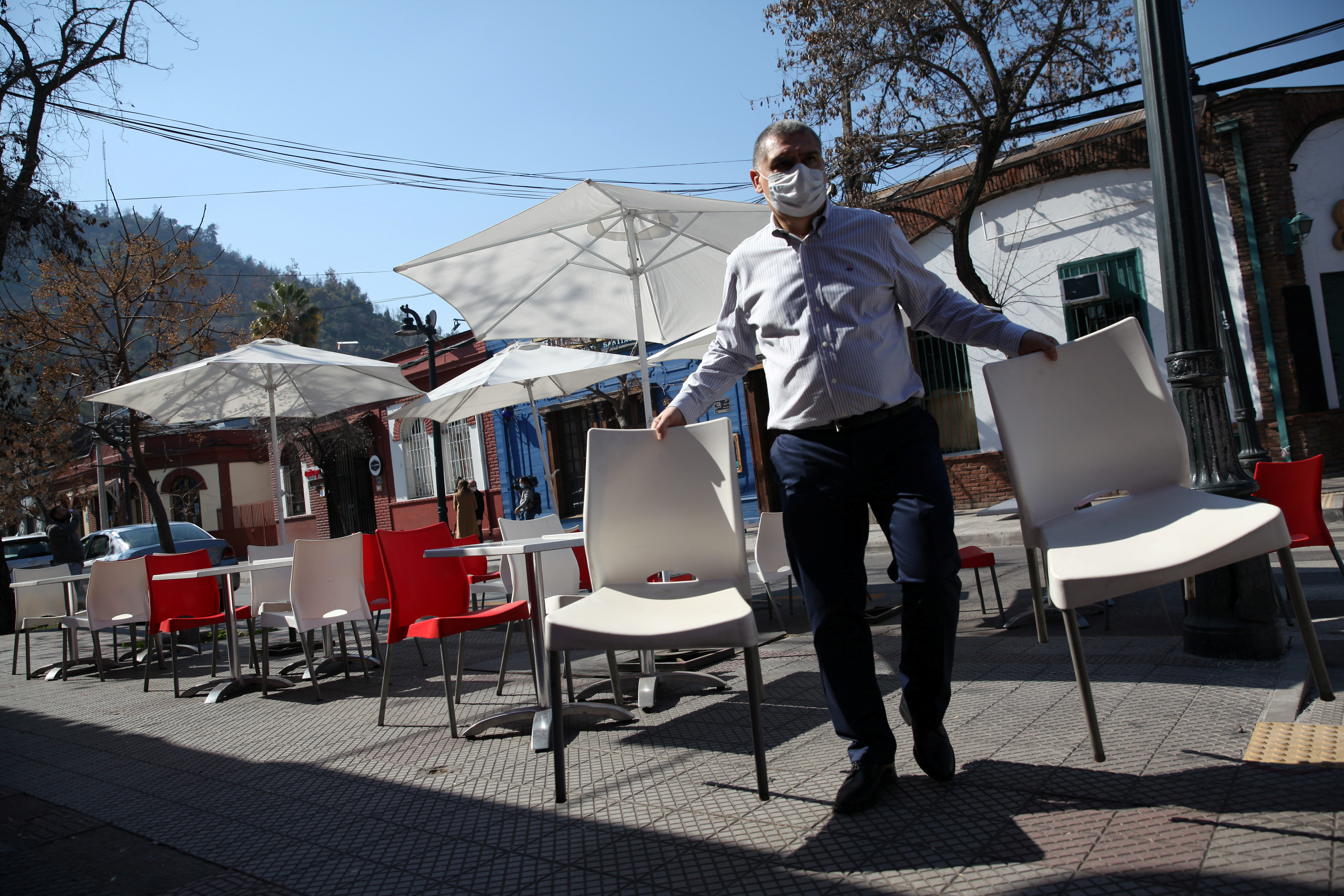 A man arranges furniture at a restaurant preparing to reopen as Chile's government allows outdoor servicing in restaurants after easing some lockdown measures put in place during the coronavirus disease (COVID-19) outbreak, in Santiago, Chile August 31, 2020. REUTERS/Ivan Alvarado - RC27PI9JK9XW