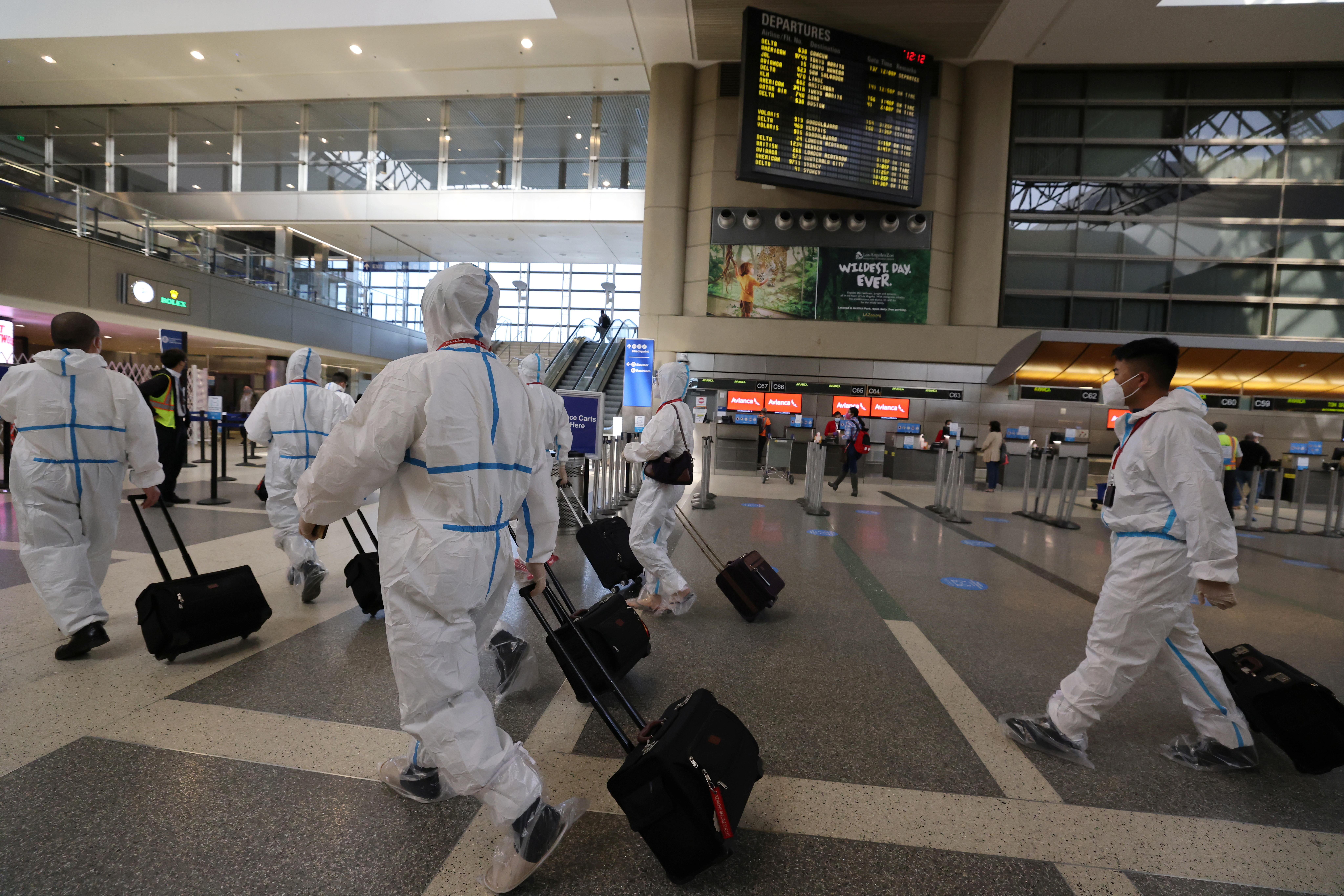 A flight crew walks through Tom Bradley international terminal at LAX airport, as the global outbreak of the coronavirus disease (COVID-19) continues, in Los Angeles, California, U.S., November 23, 2020. REUTERS/Lucy Nicholson - RC2B9K9555U7