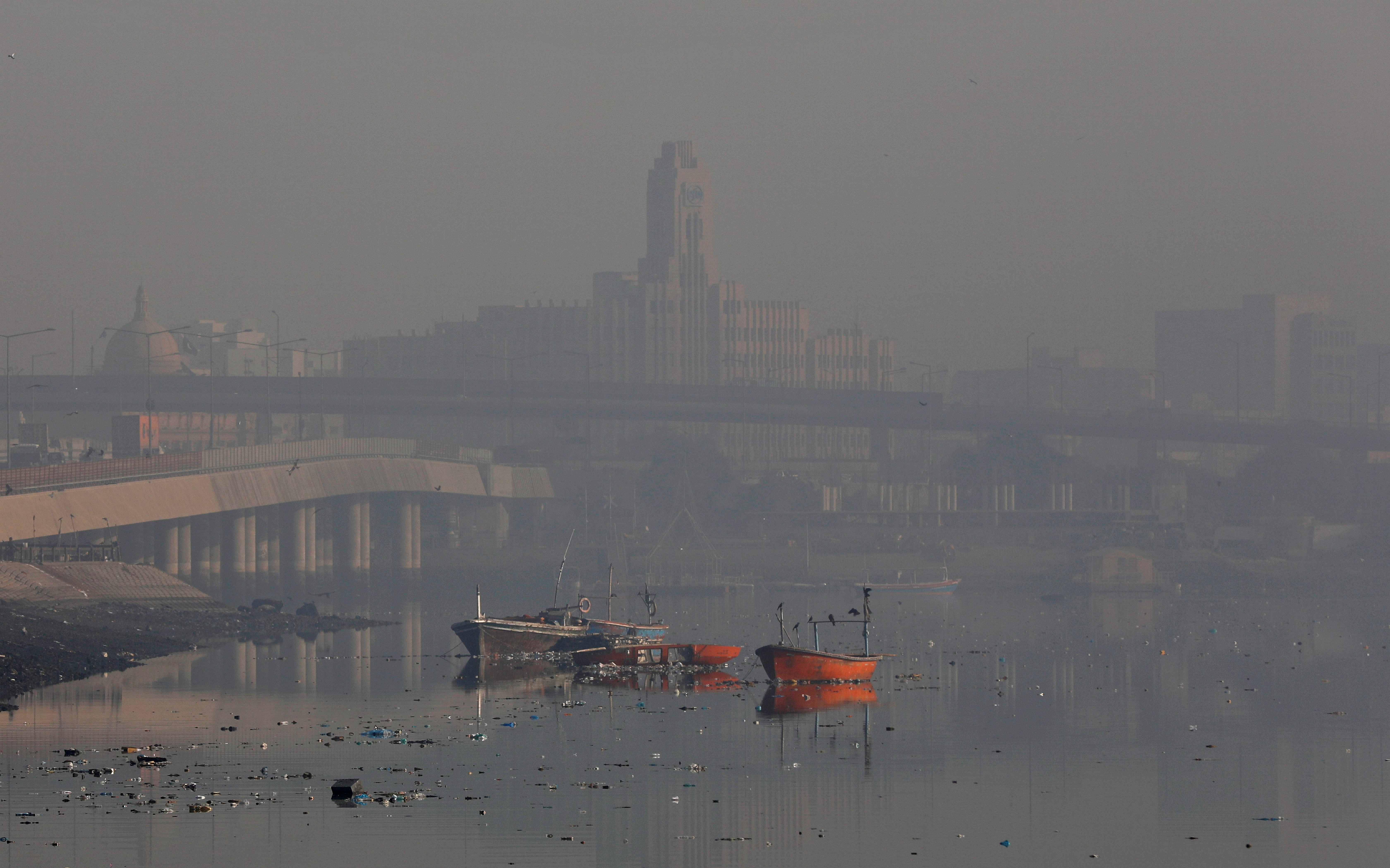 A general view of boats amid dense fog and mist in the background during morning hours at China Creek area in Karachi, Pakistan January 17, 2020. REUTERS/Akhtar Soomro - RC2JHE9XUAJG