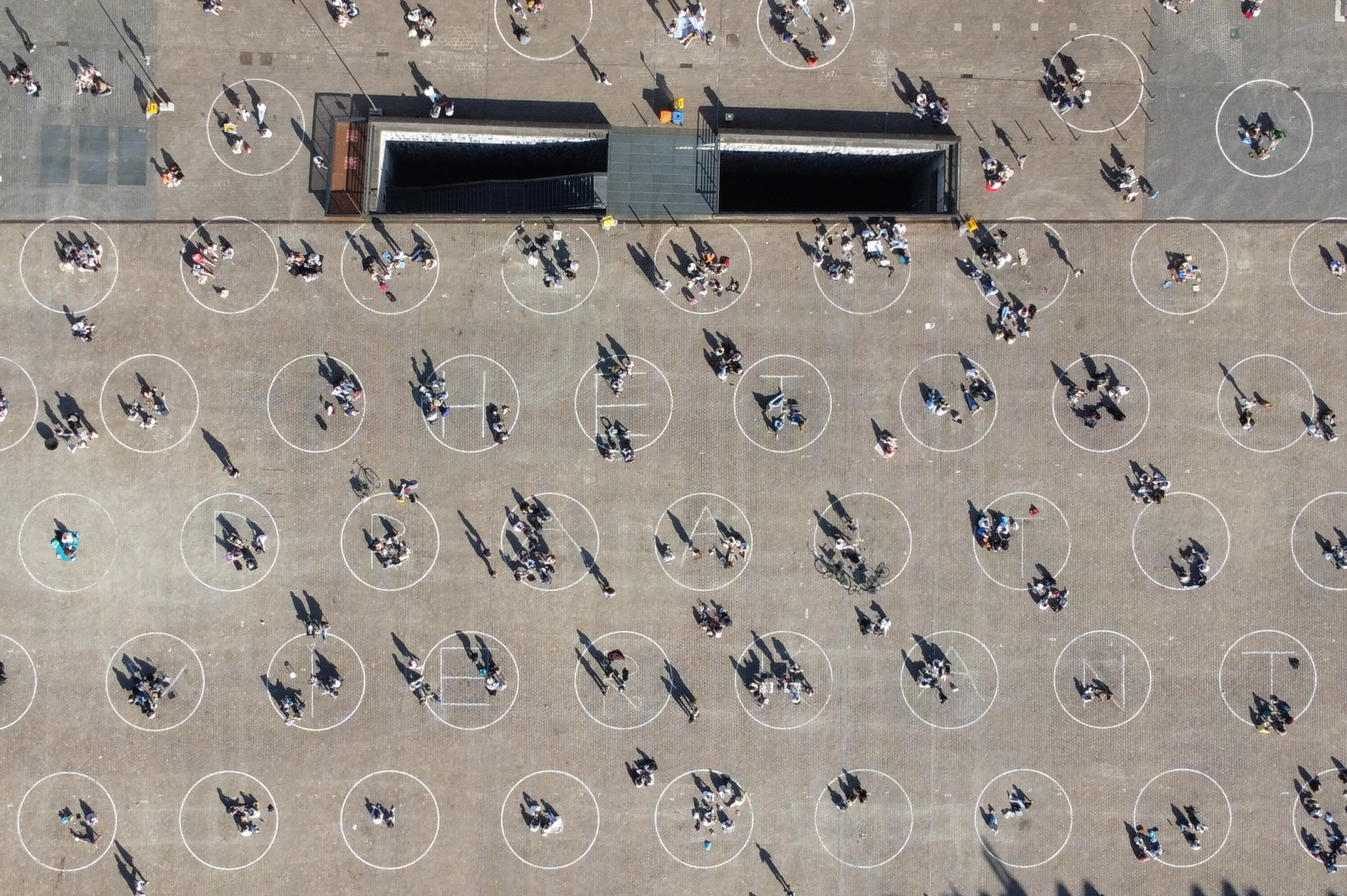 People relax inside circles painted by local authorities at Saint Peter's Square (Sint-Pietersplein) to encourage respect in social distancing amid the coronavirus (COVID-19) outbreak, in Ghent, Belgium March 29, 2021. Picture taken with a drone on March 29, 2021. REUTERS/Bart Biesemans - RC2PLM9SHZ2I