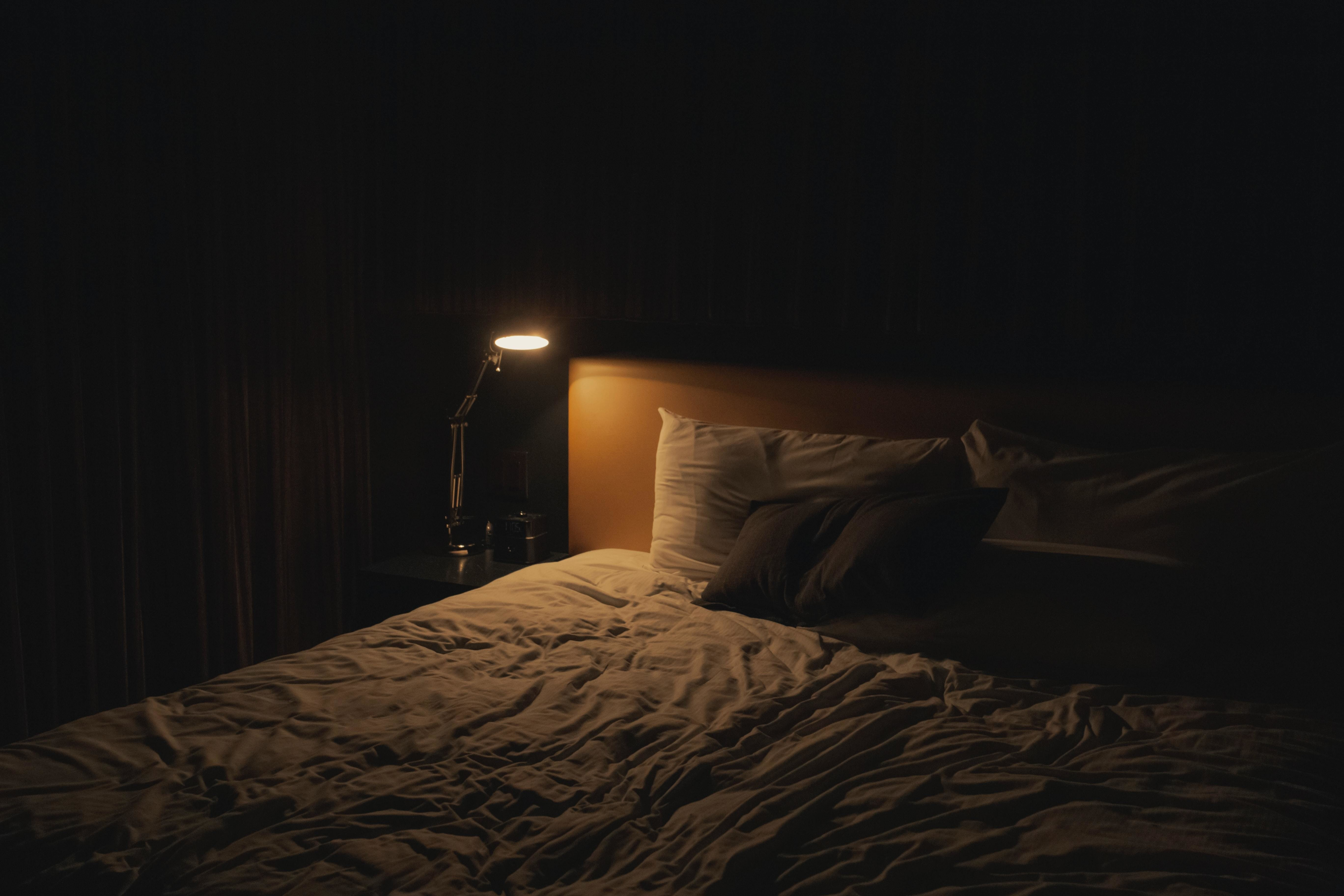 a picture of a bedside table with a lamp on it shining its light over a bed