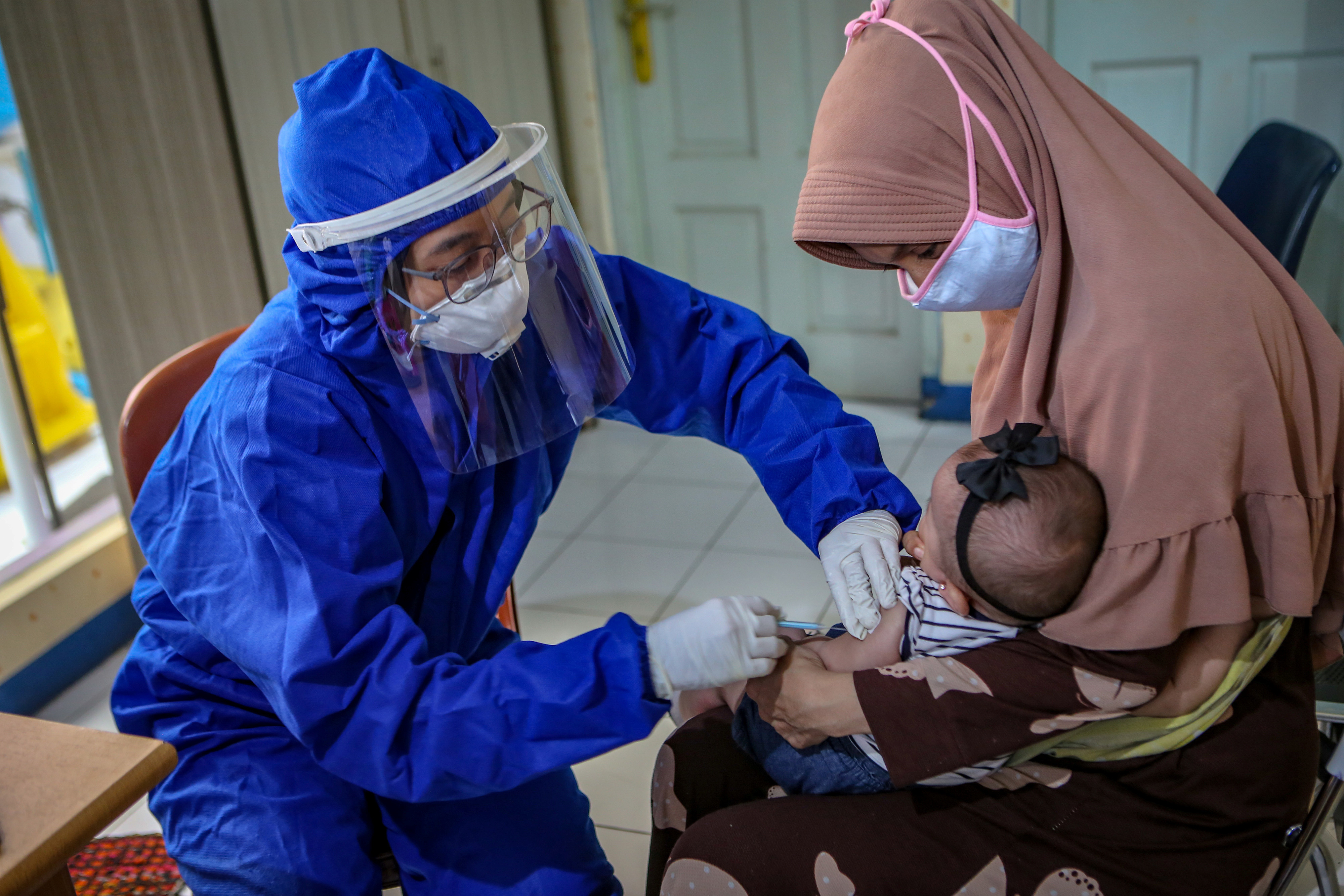 A medical staff member wearing personal protective equipment (PPE) vaccinates a baby, amid the coronavirus disease (COVID-19) outbreak, in Tangerang, near Jakarta, Indonesia May 13, 2020.  Antara Foto/Fauzan/ via REUTERS   ATTENTION EDITORS - THIS IMAGE HAS BEEN SUPPLIED BY A THIRD PARTY. MANDATORY CREDIT. INDONESIA OUT. NO COMMERCIAL OR EDITORIAL SALES IN INDONESIA. - RC2ONG9SDX7M