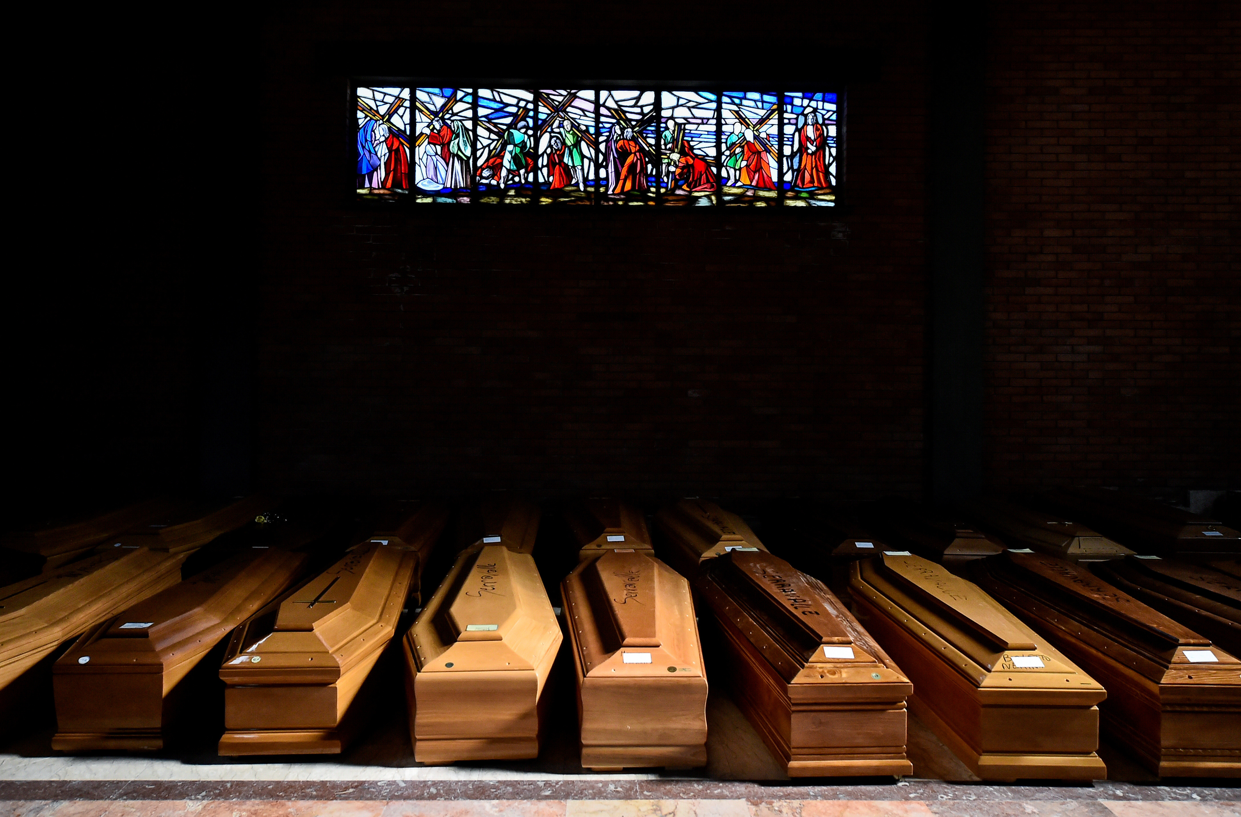 Coffins of people who have died from coronavirus disease (COVID-19) are seen in the church of the Serravalle Scrivia cemetery, which like many places in northern Italy is struggling to cope with the number of deaths from the virus that is growing every day, in Alessandria, Italy, March 23, 2020. REUTERS/Flavio Lo Scalzo     TPX IMAGES OF THE DAY - RC2RPF9LLKDB