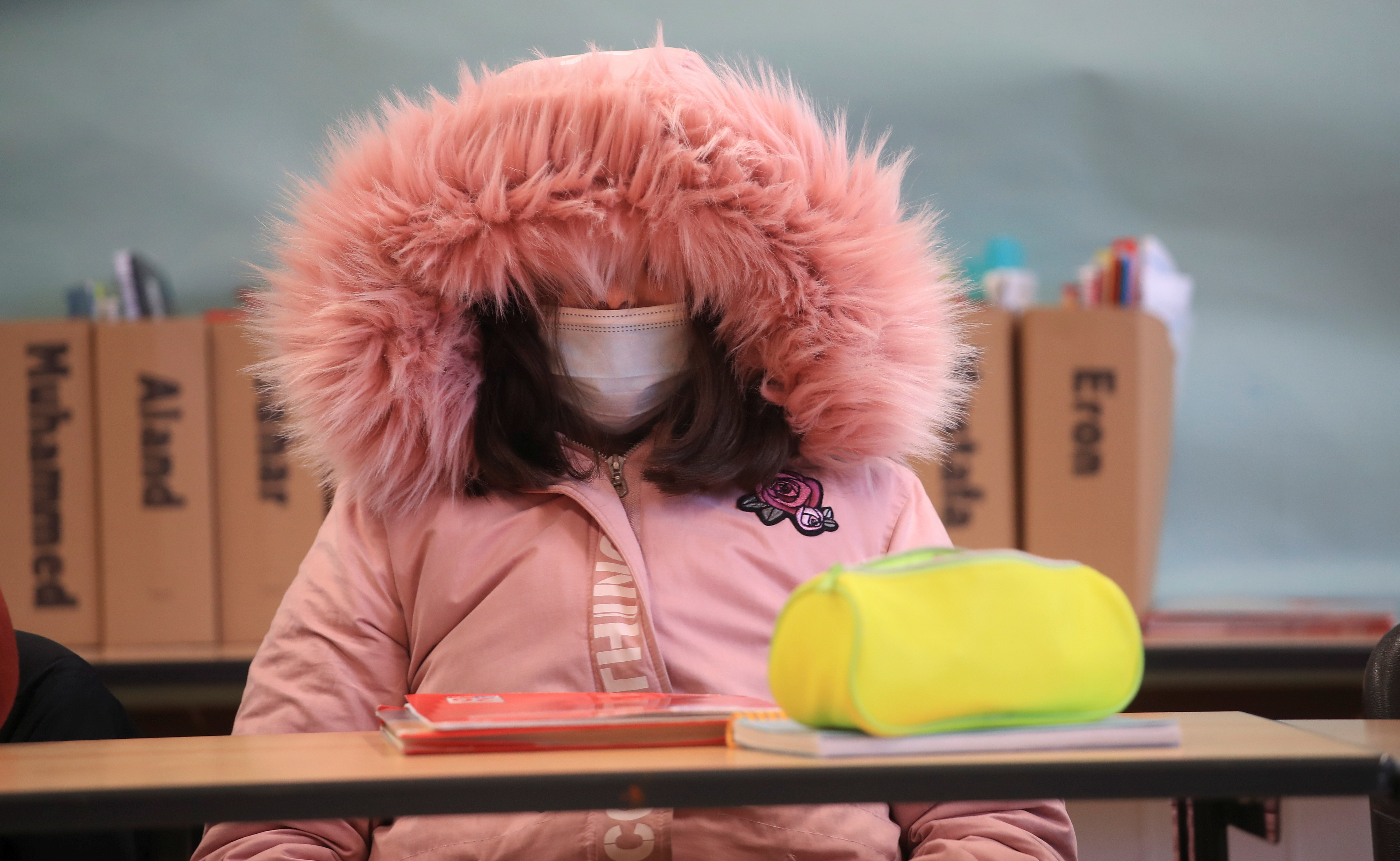 Schoolgirl of Freiherr-vom-Stein secondary school in the North Rhine-Westphalian city Bonn wears a winter outfit against the cold as school resumes with open windows and protective masks against the spread of COVID-19 following the autumn holidays in Germany, October 26, 2020. REUTERS/Wolfgang Rattay - RC2AQJ937173