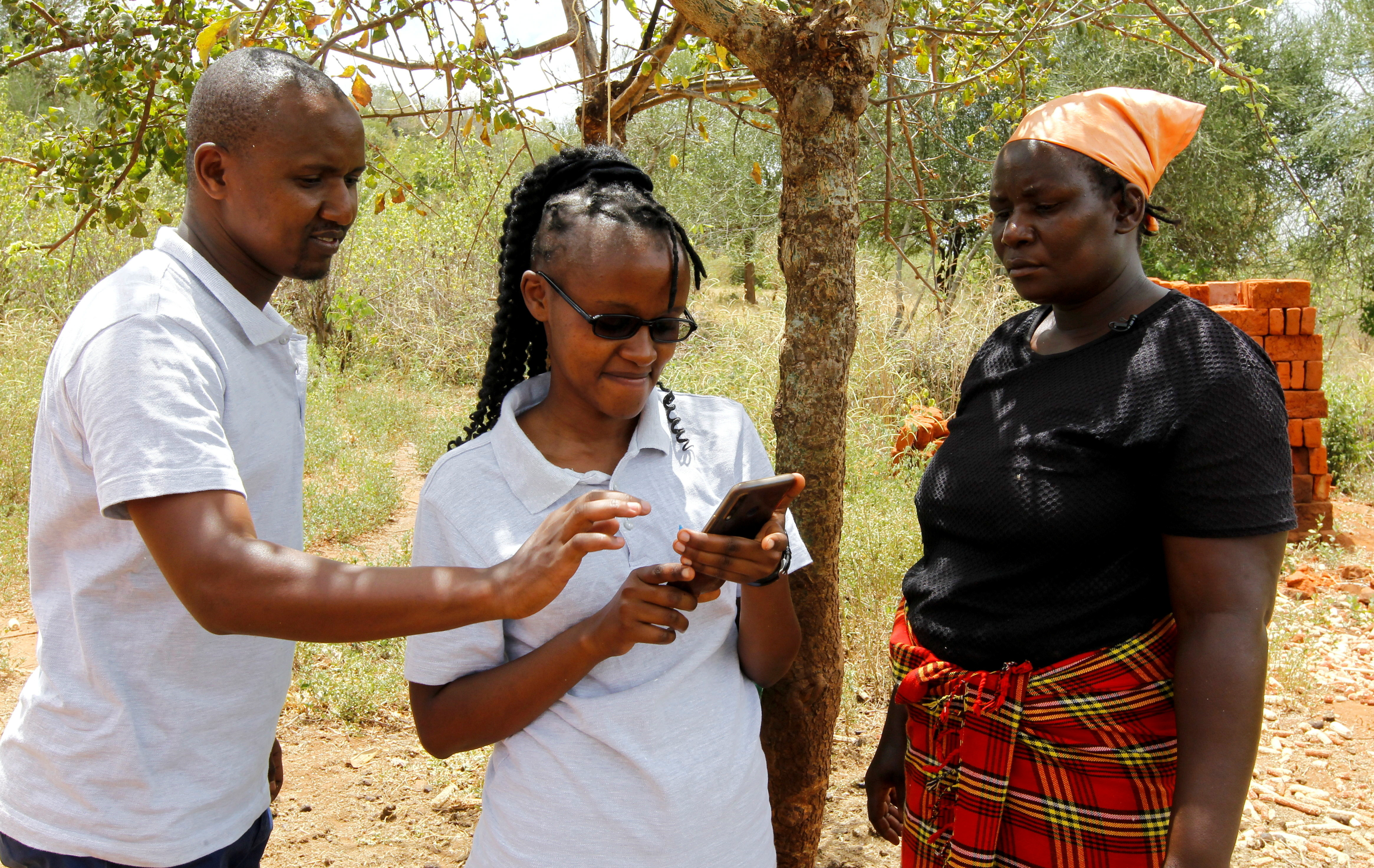 Pula operations manager Daniel Mbuvi and field officer Ruth Wambua update details of farmer Waki Munyalo in an app after collecting harvest insured by Pula, an agricultural insurance company that helps small-scale farmers manage the risk associated with extreme climate conditions, in Kitui county, Kenya, March 17, 2021. Picture taken March 17, 2021. REUTERS/Monicah Mwangi - RC2LZM9TFV6Q
