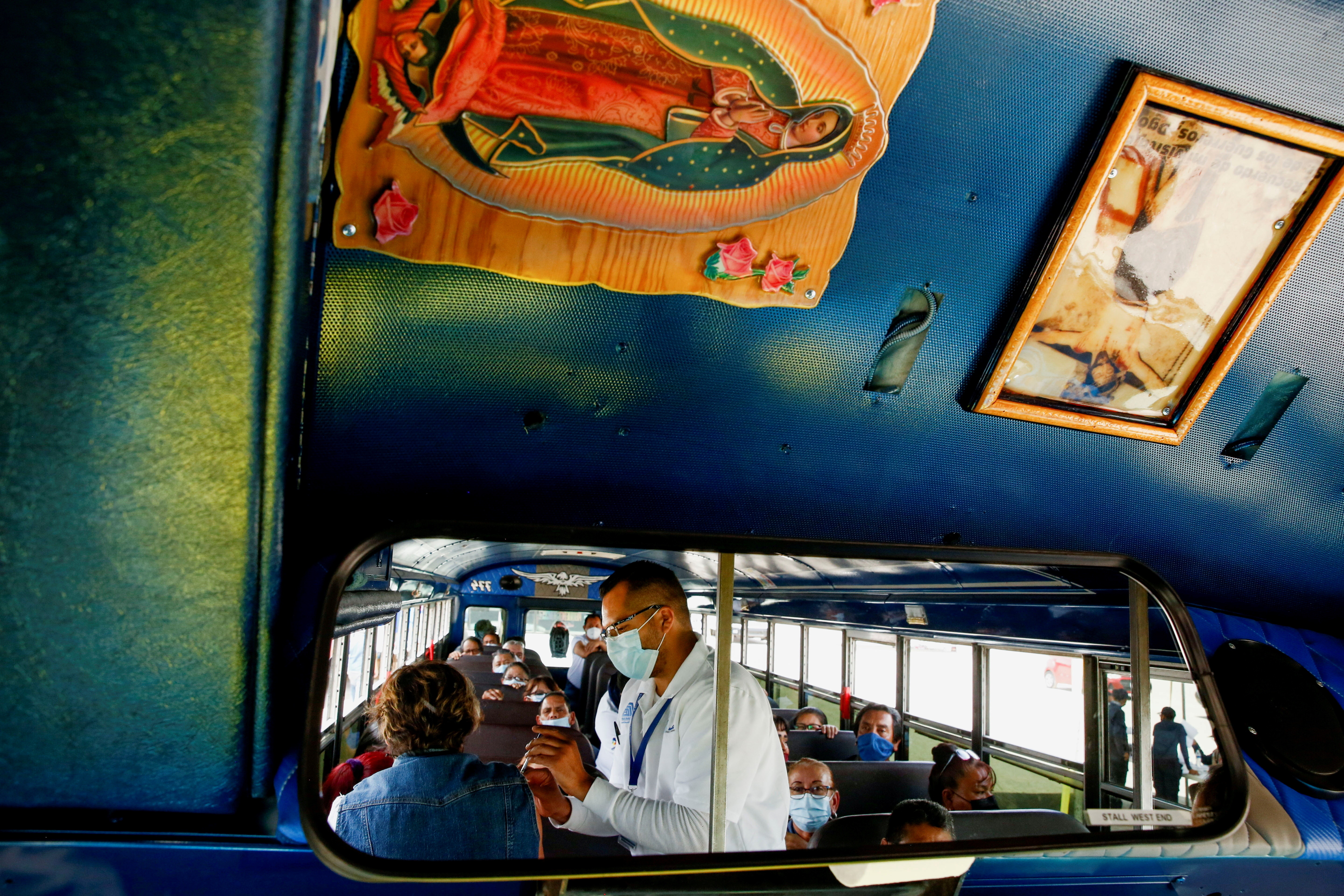 Employees of an assembly factory are seen reflected in the mirror of a bus as they receive a dose of the Pfizer-BioNTech coronavirus disease (COVID-19) vaccine in Ciudad Juarez, Mexico May 24, 2021. REUTERS/Jose Luis Gonzalez     TPX IMAGES OF THE DAY - RC2EMN9IJ0JC
