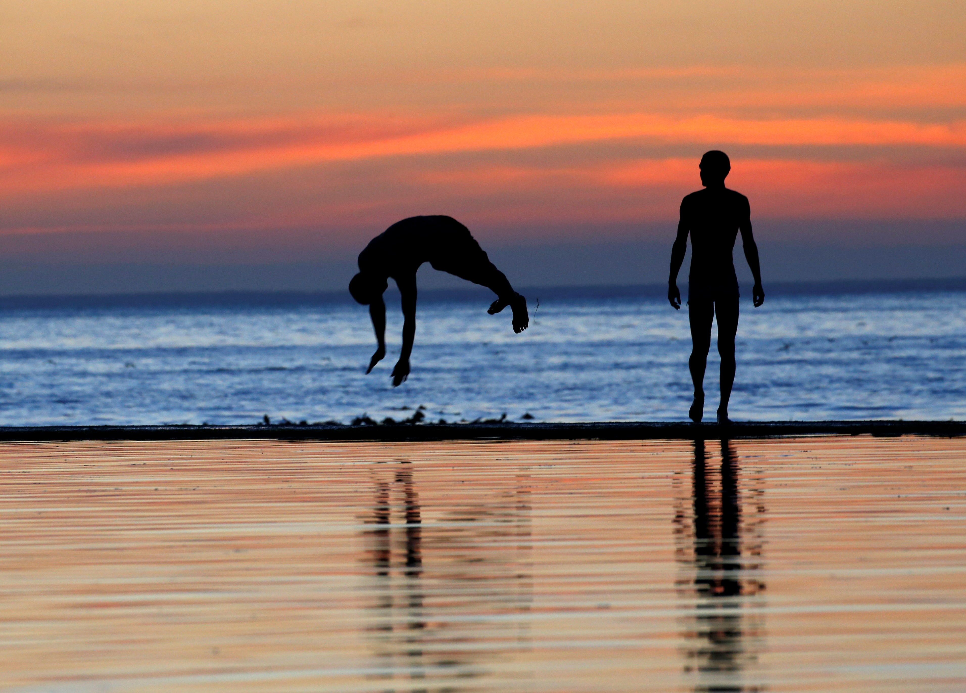 Youths dive into a tidal pool as temperatures soar at Camps Bay beach in Cape Town, South Africa, December 11, 2016.   REUTERS/Mike Hutchings - RC141A86A530