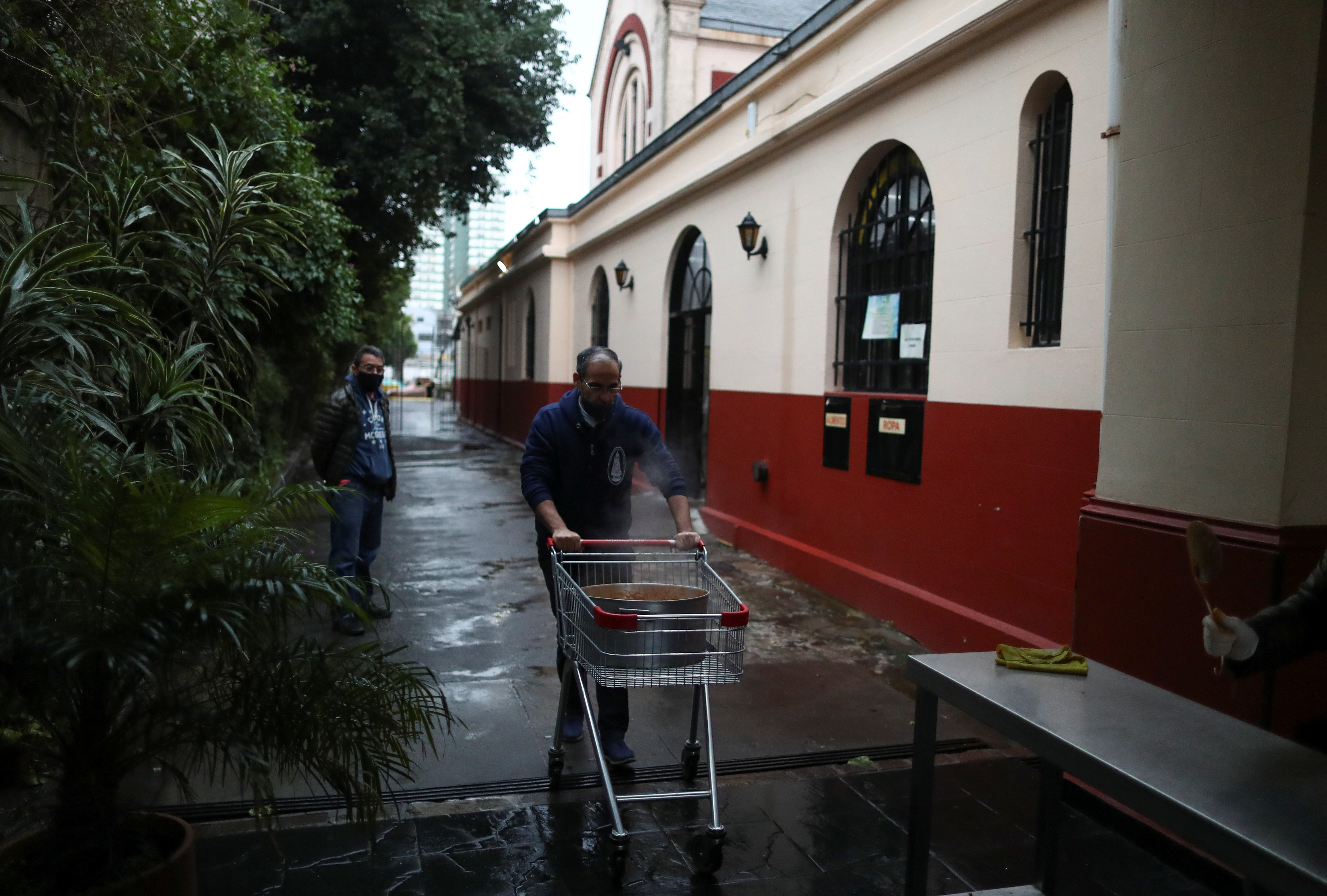 Father Eusebio Hernandez Greco pushes a cart with a pot of stew at a soup kitchen organized at the Caacupe church, during the coronavirus disease (COVID-19) outbreak, in Buenos Aires, Argentina July 23, 2020. Picture taken July 23, 2020. REUTERS/Agustin Marcarian - RC2N7I9S500P