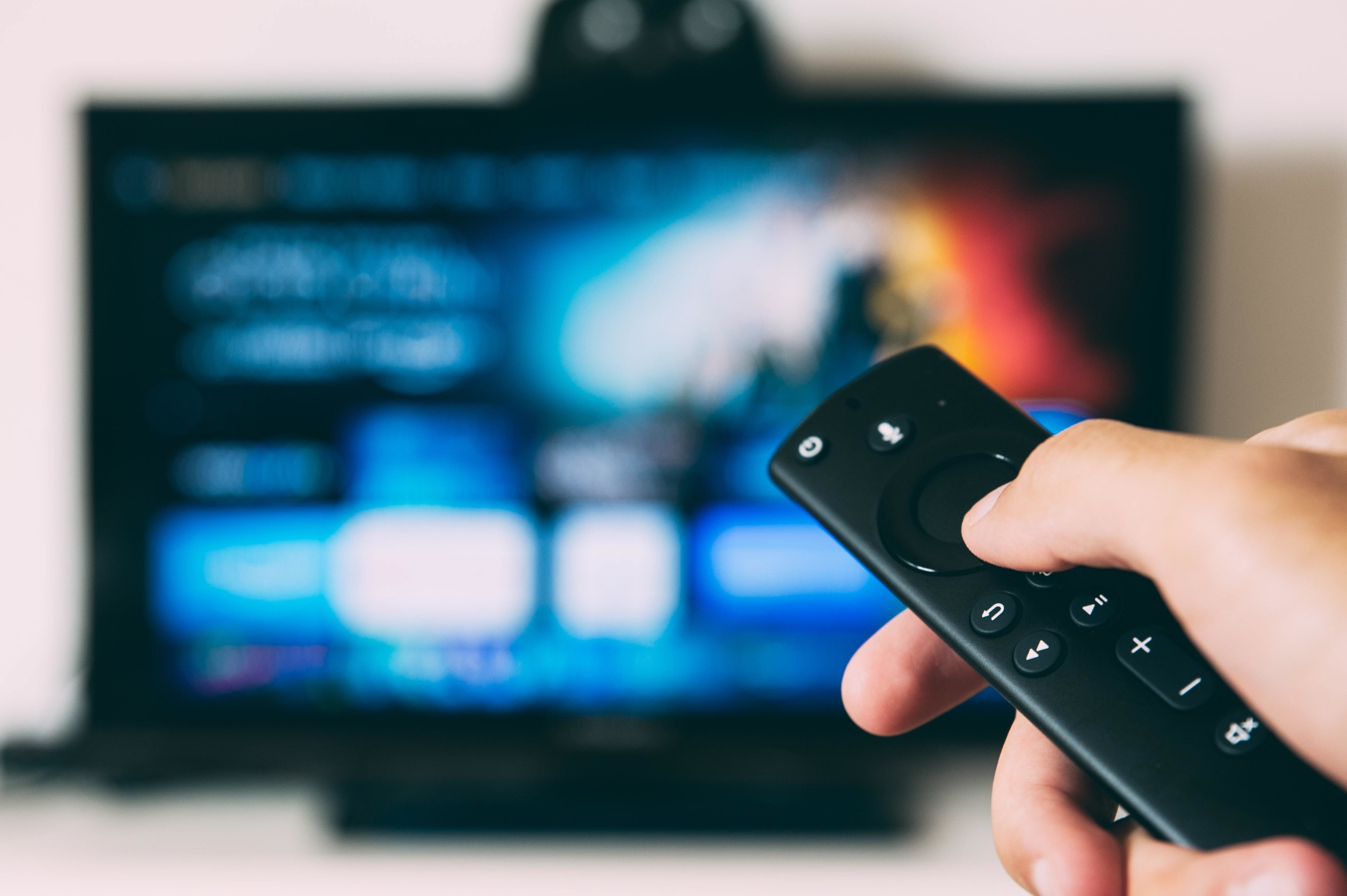 a picture of a hand controlling a remote control pointed at a television
