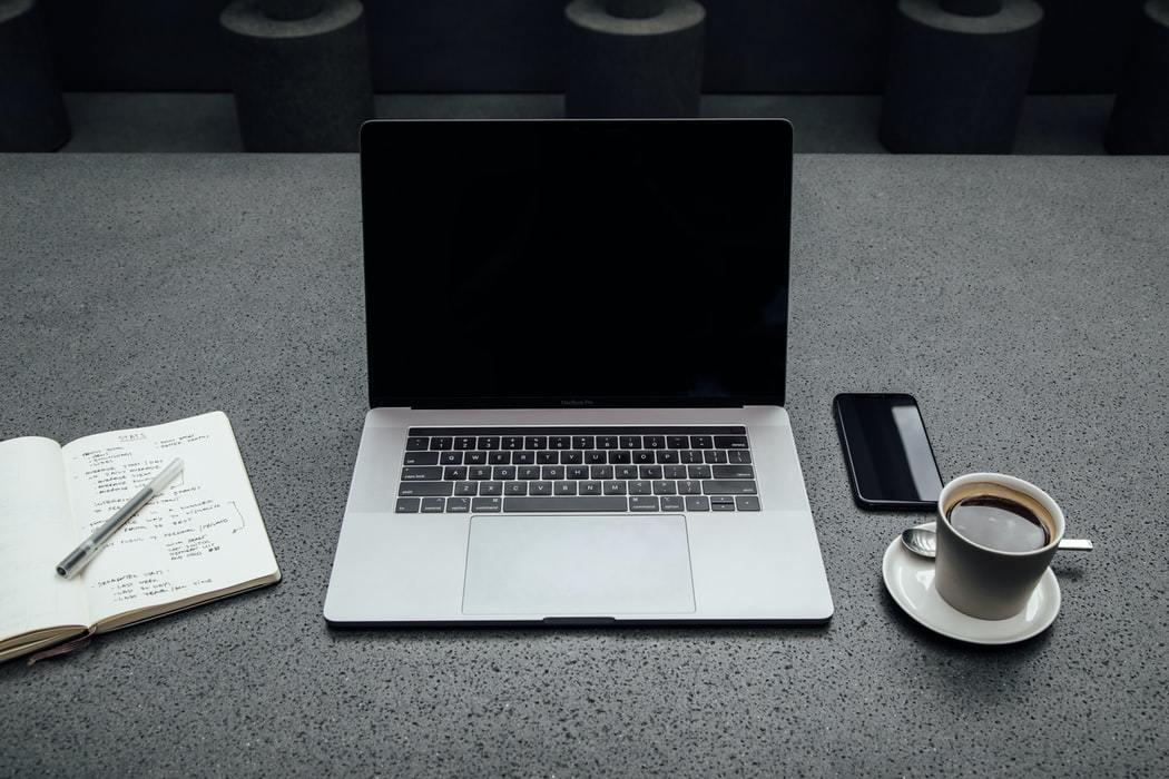 image of a work station with a laptop, notebook etc