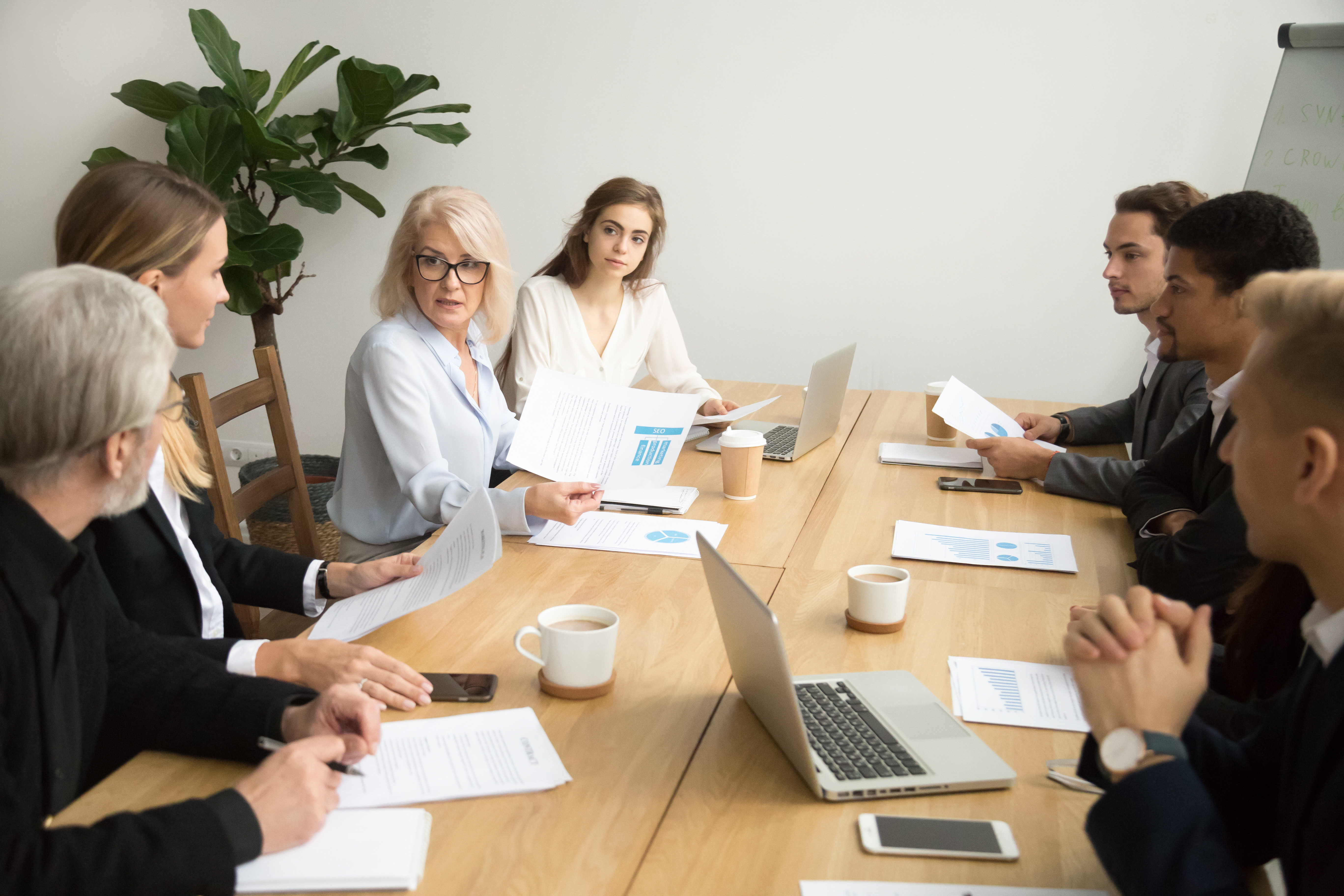 Serious aged businesswoman discussing corporate financial report with team talking to employees, senior mature female boss ceo leader analyzing work results with subordinates at company group meeting