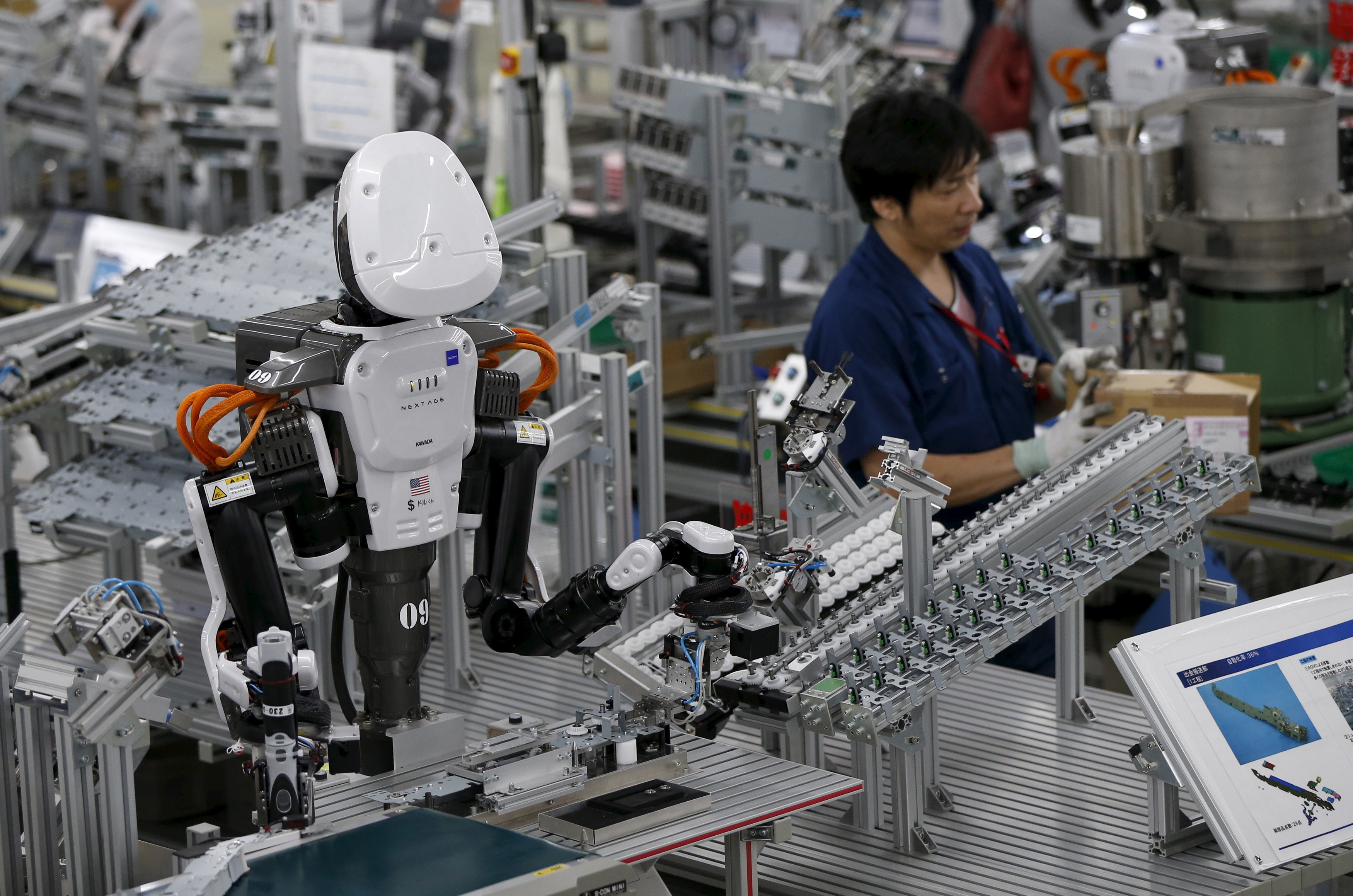 A humanoid robot works side by side with employees in the assembly line at a factory of Glory Ltd., a manufacturer of automatic change dispensers, in Kazo, north of Tokyo, Japan, July 1, 2015. Japanese firms are ramping up spending on robotics and automation, responding at last to premier Shinzo Abe's efforts to stimulate the economy and end two decades of stagnation and deflation. Picture taken July 1, 2015. REUTERS/Issei Kato - GF10000147193