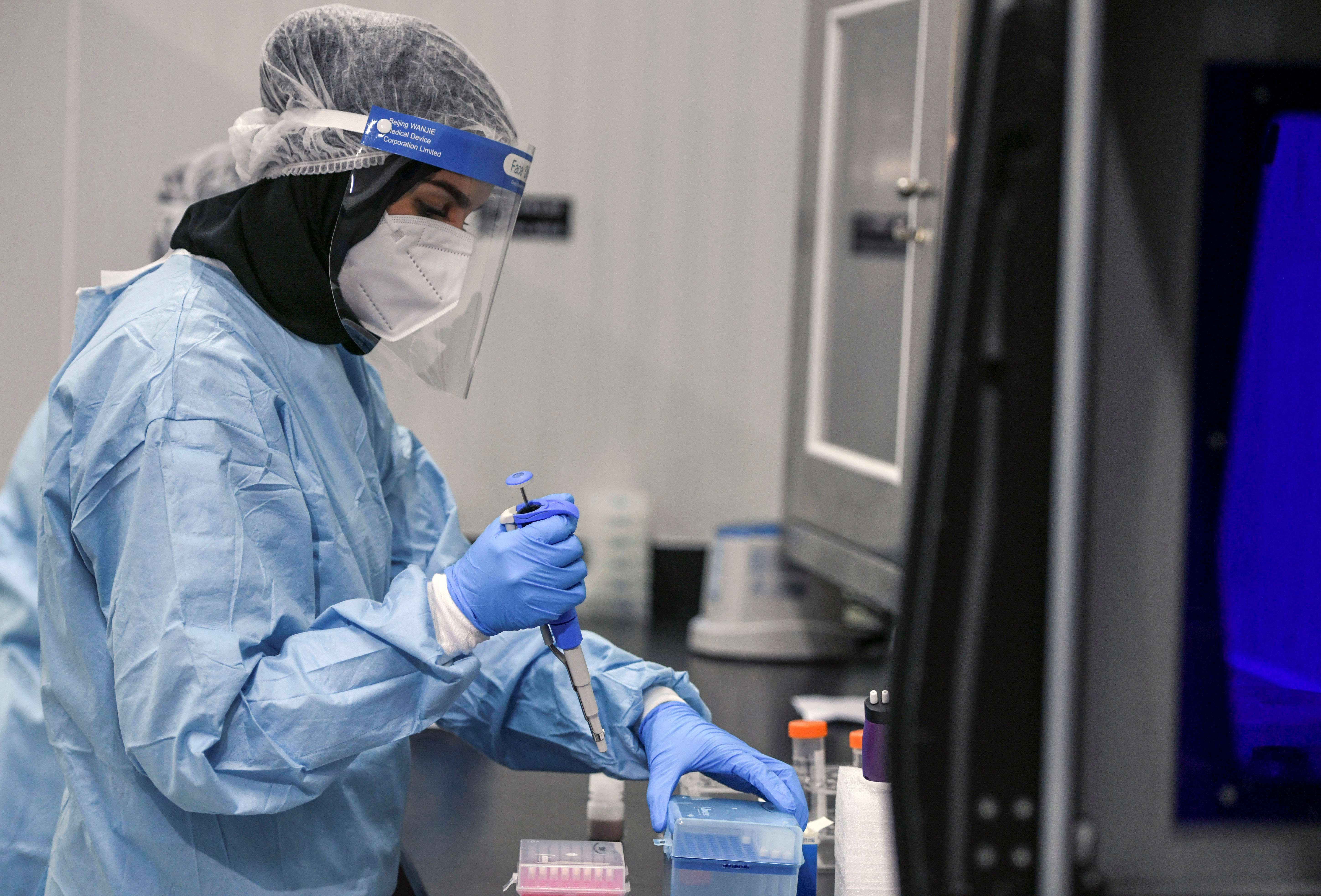 A medical worker wearing protective suit and face shield carries out tests at the Biogenix Laboratories, which performs COVID-19 detection tests, in Masdar City, Abu Dhabi, United Arab Emirates, October 6, 2020. Picture taken October 6, 2020. REUTERS/Khushnum Bhandari. - RC2AEJ9F1STJ