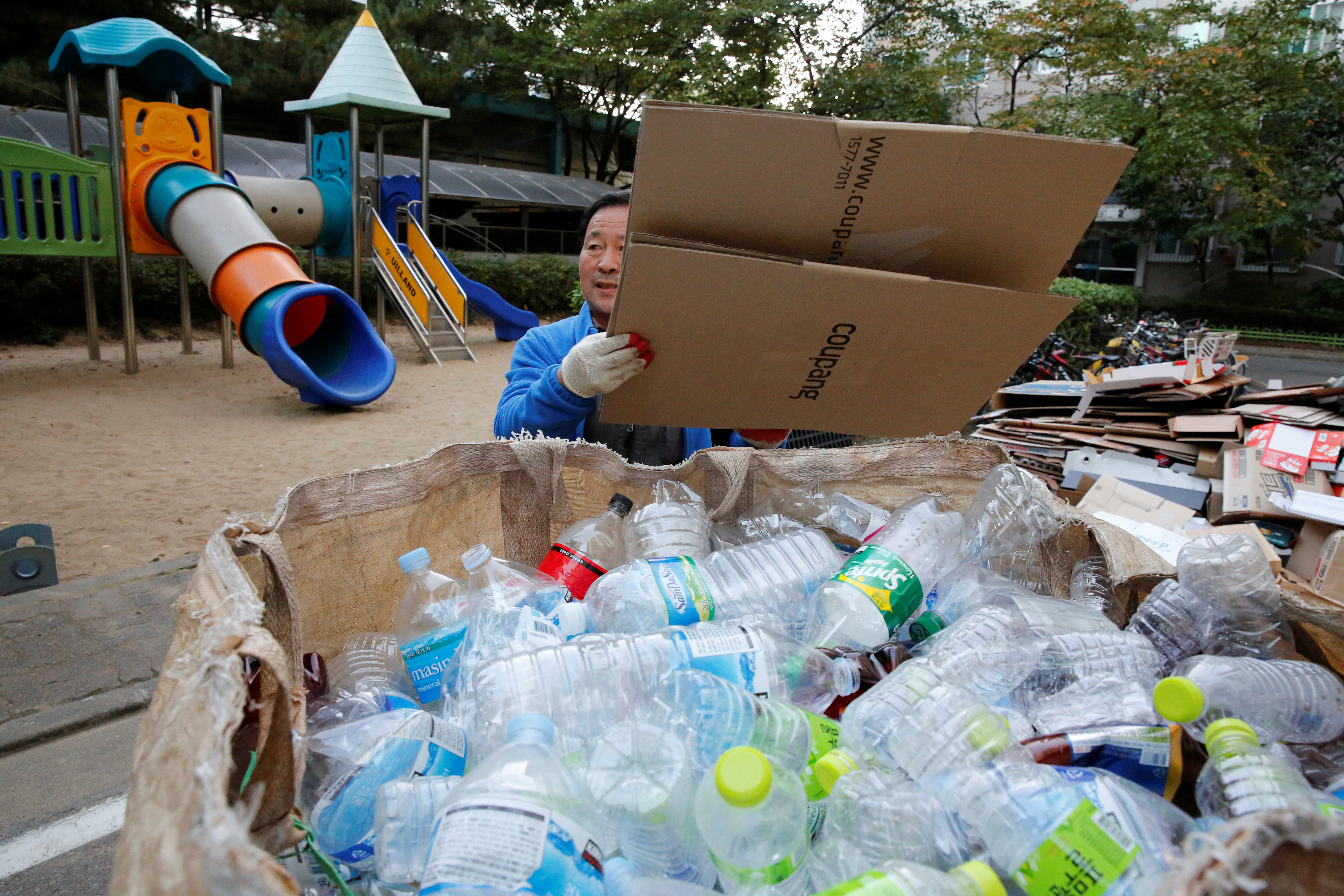 Lee Yong-gi, owner of a recycling facility, collects recycling garbage at an apartment area in Seoul, South Korea, October 23, 2020. Picture taken October 23, 2020.    REUTERS/Heo Ran - RC2DXJ912670