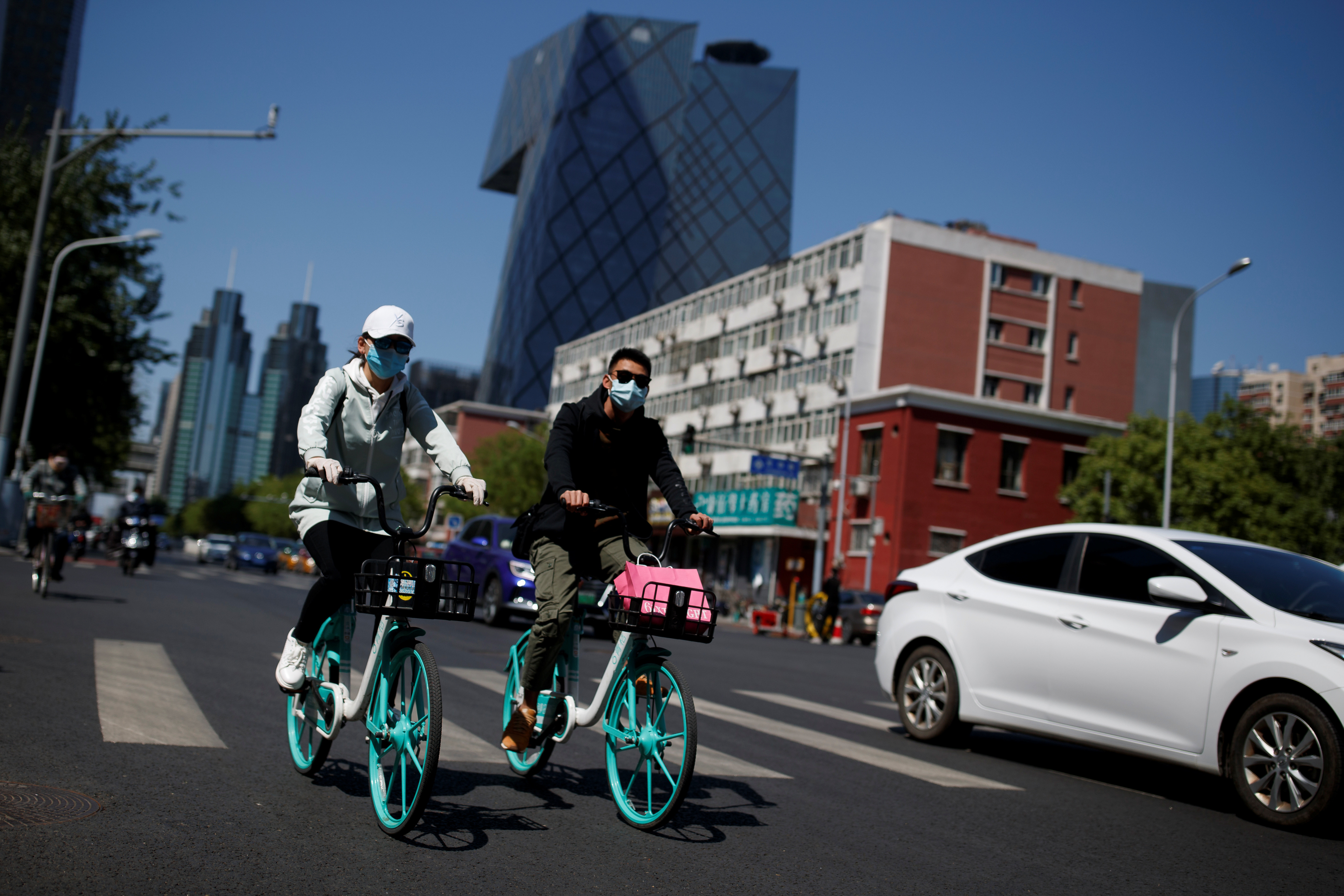 "People wearing protective masks ride bikes in the Central Business District on a ""blue sky day"" in Beijing, as the spread of the novel coronavirus disease (COVID-19) continues, in China April 22, 2020. REUTERS/Thomas Peter - RC2M9G97ENBP"