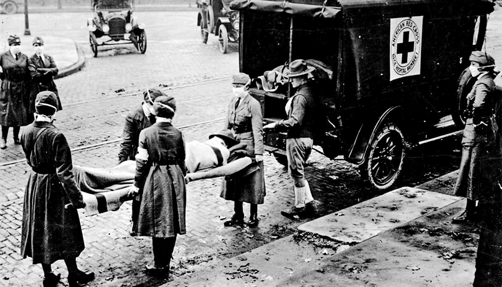 A photo of a body being lifted on a stretcher into an ambulance, during the 1918 flu pandemic